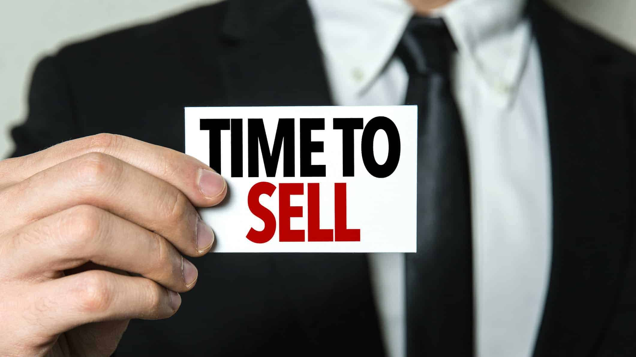 business man holding sign stating time to sell