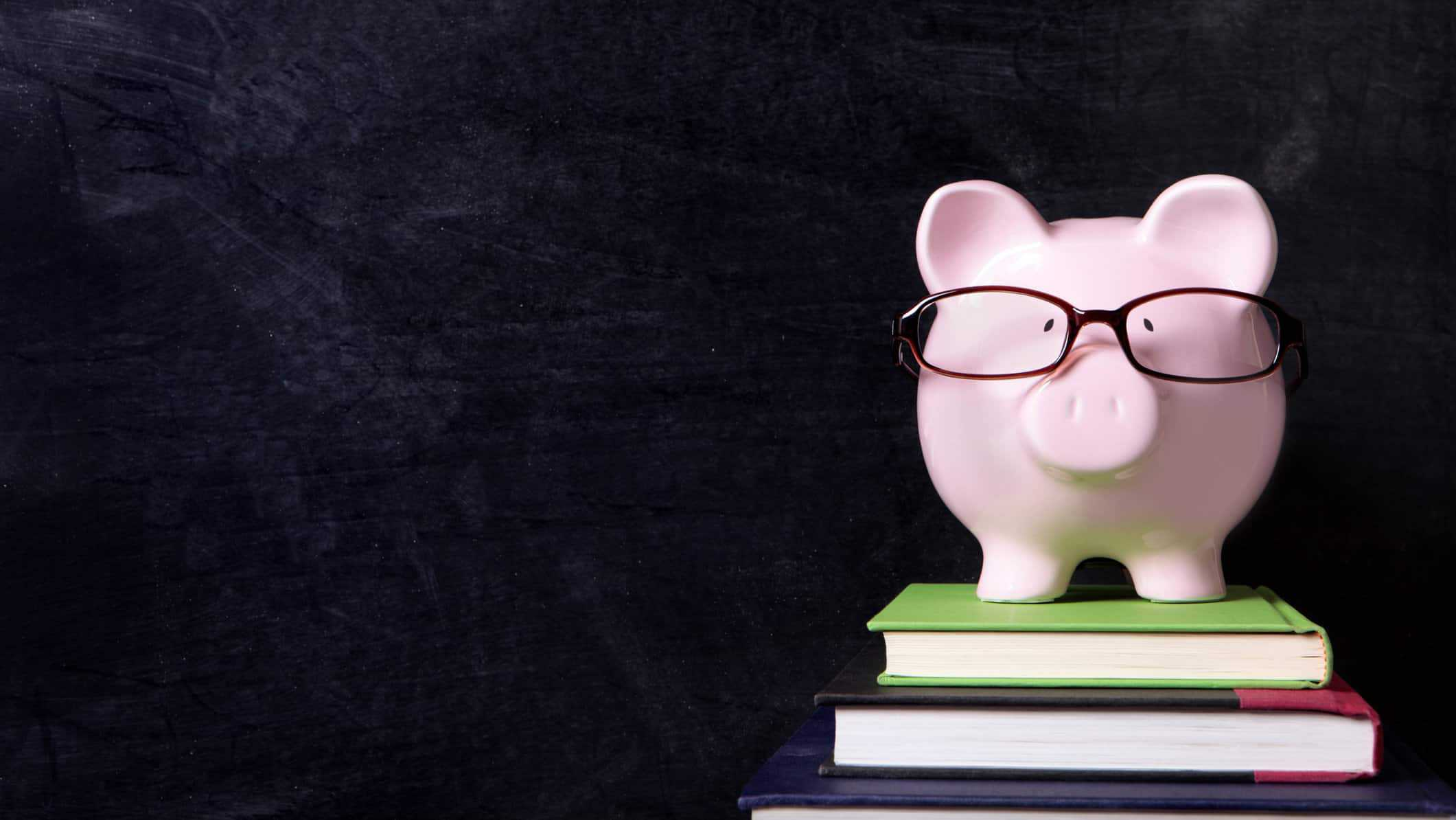 Piggy bank wearing glasses sitting on pile of books