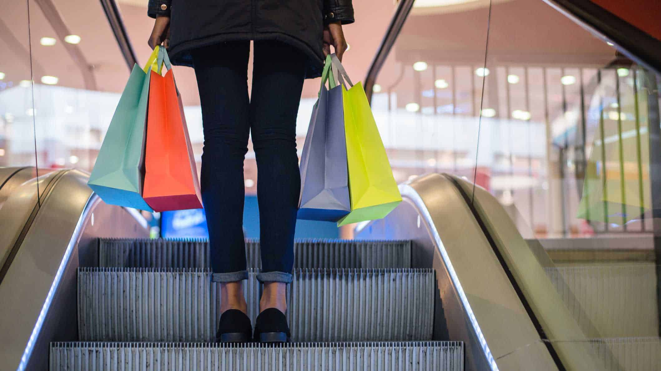 woman on escalator carrying shopping bags