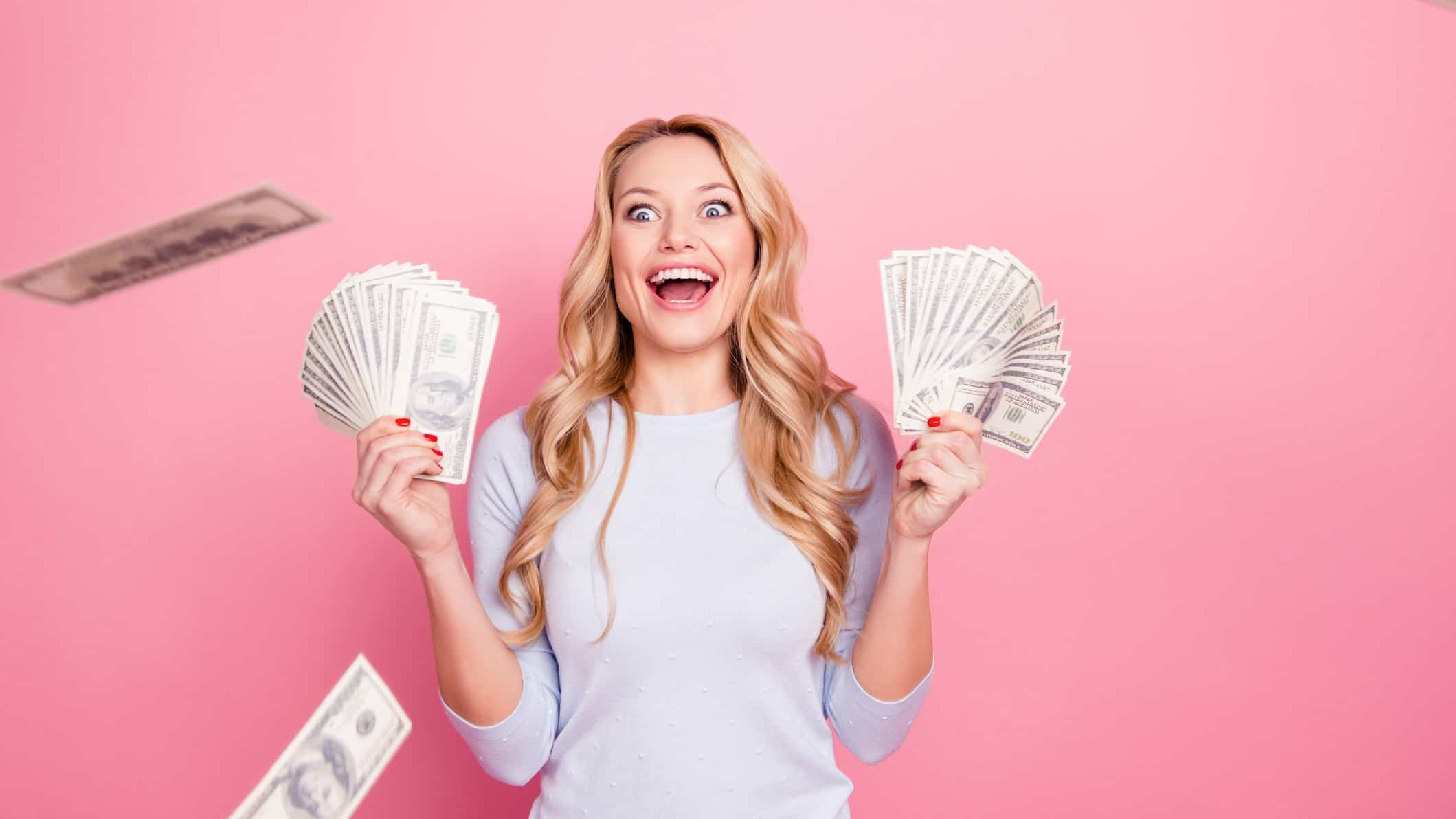 Woman holding up wads of cash
