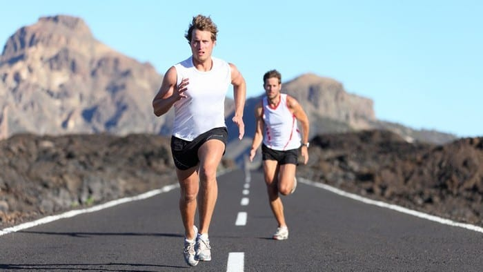 Two male runners racing down an empty road