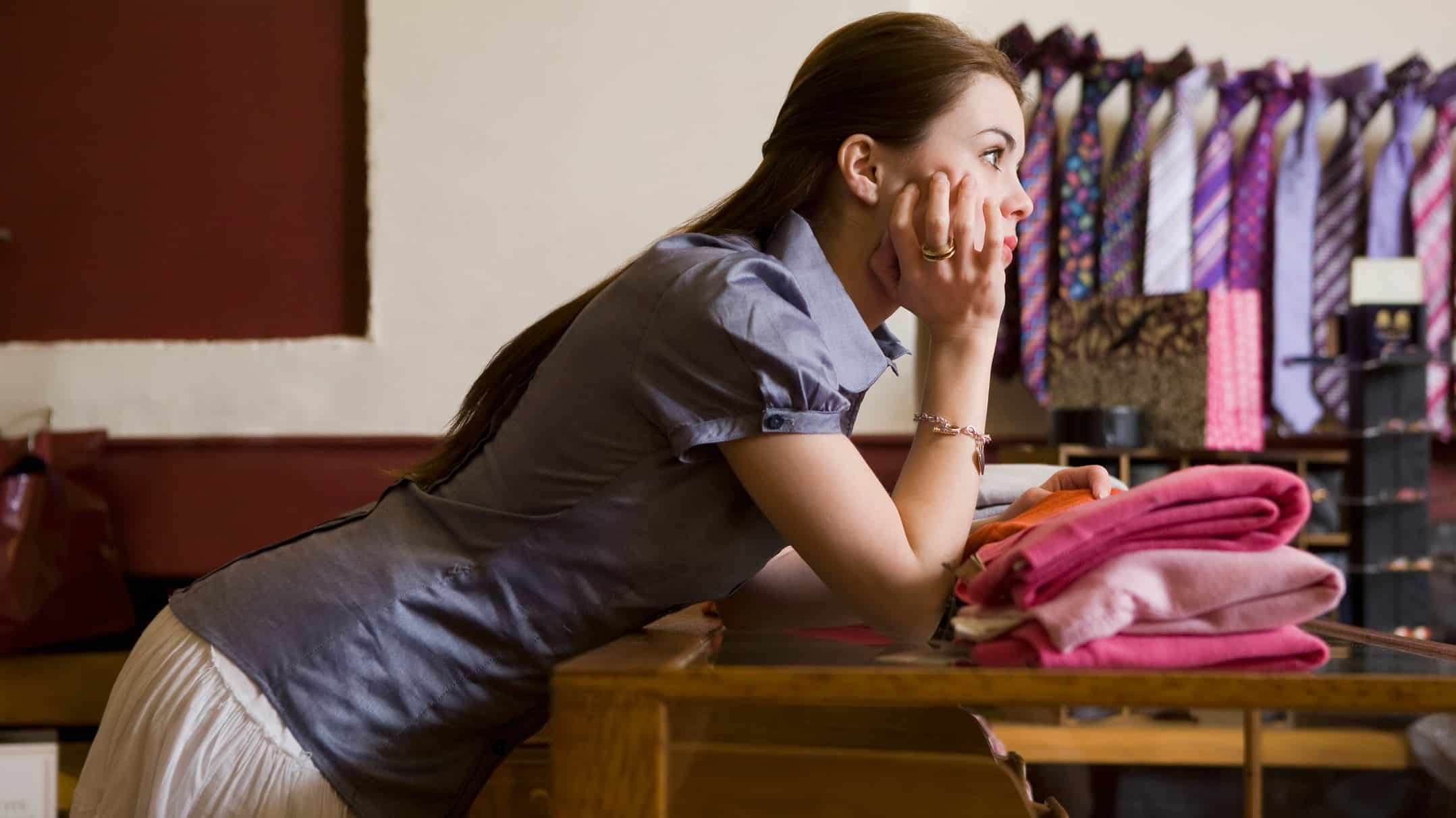 Female shop assistant bored leaning on counter