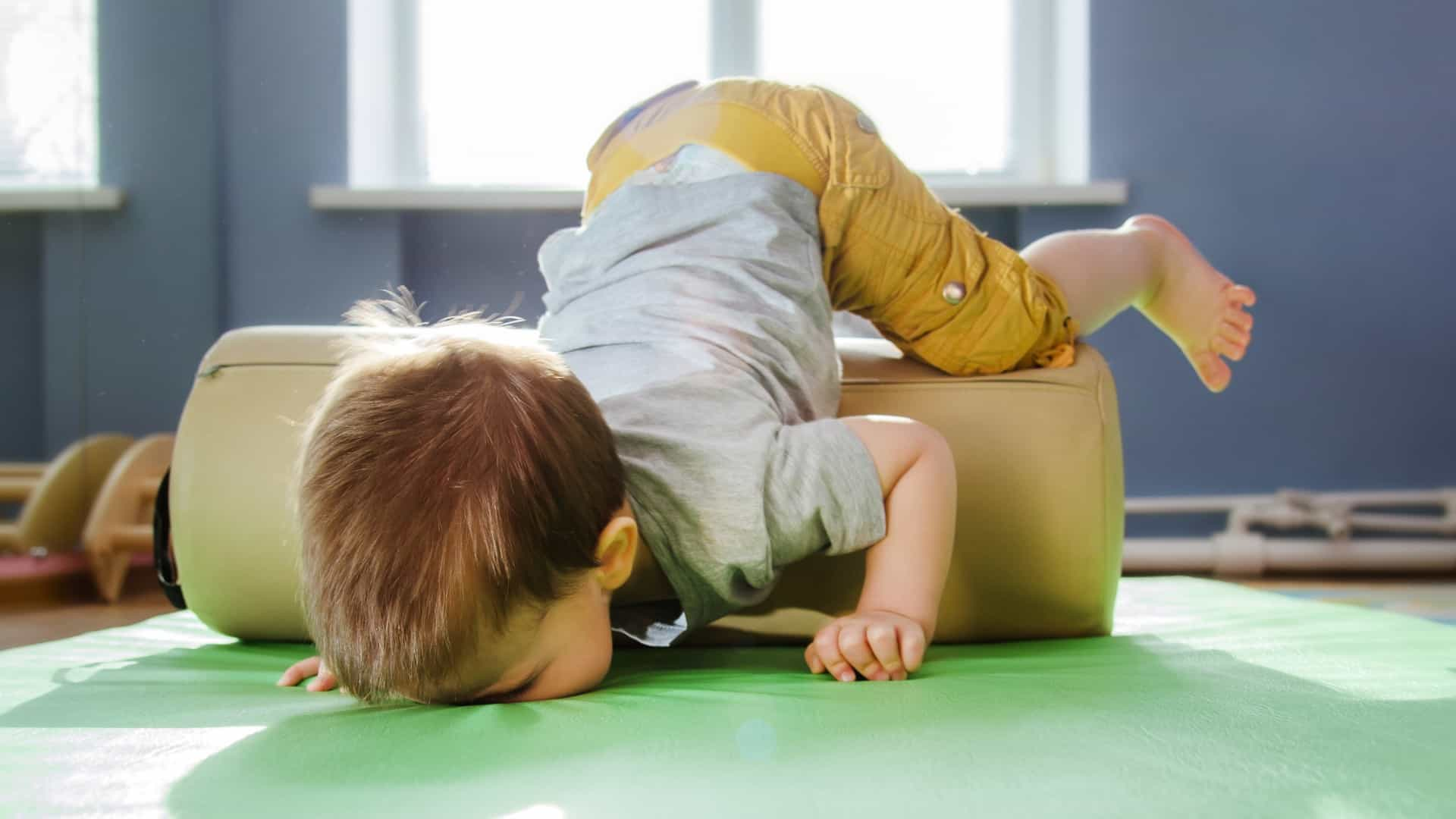 Toddler in nursery nosediving over cushion onto floor