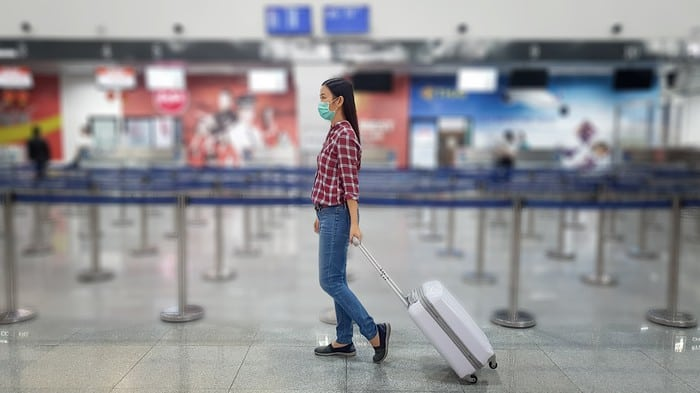 lady walking through empty airport to travel indicating tough times for travel shares