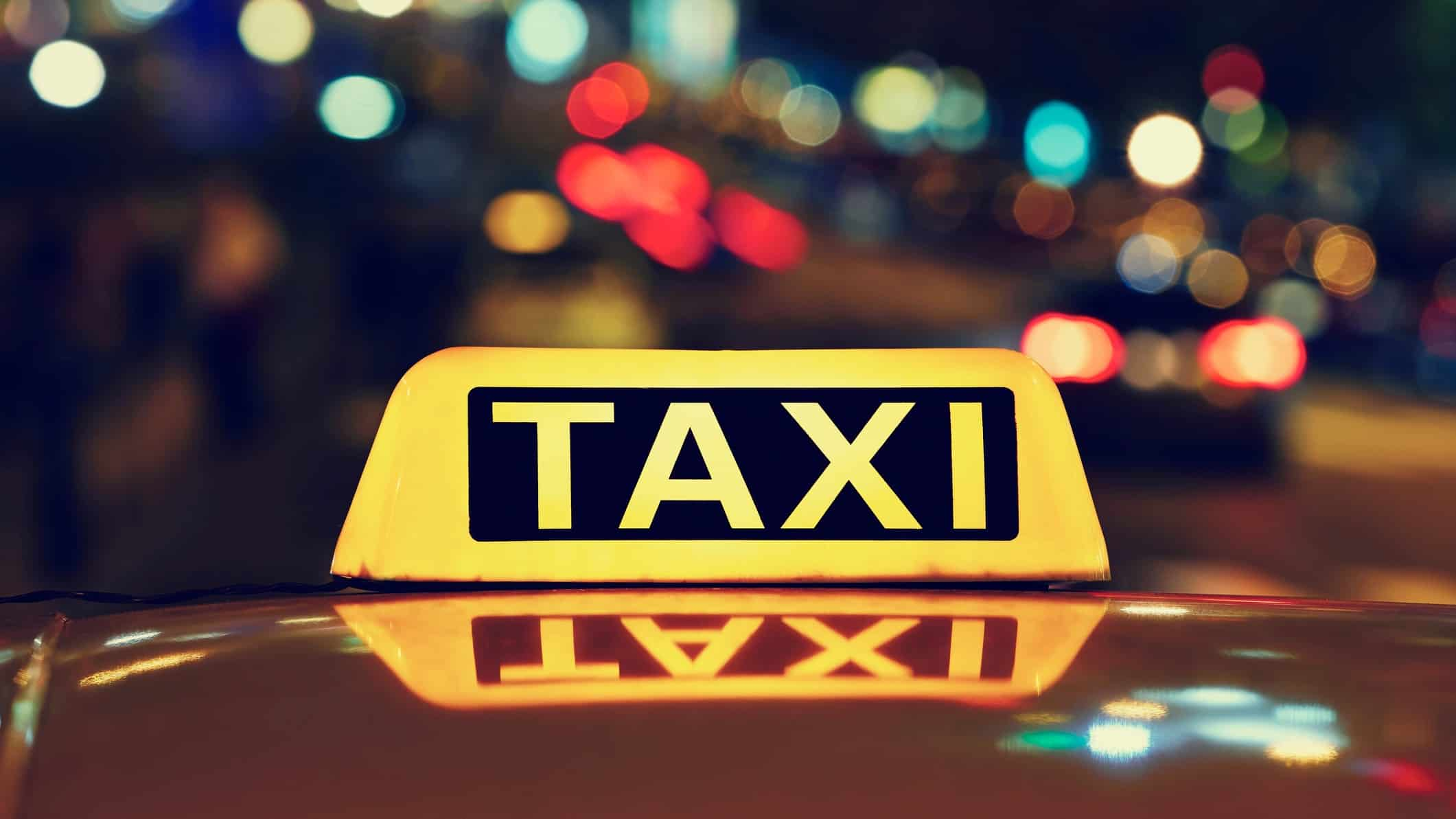 illuminated taxi sign against backdrop of city lights
