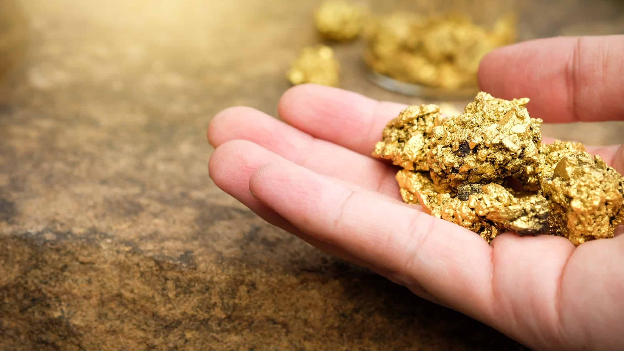 Hand holding gold nugget ASX stocks buy