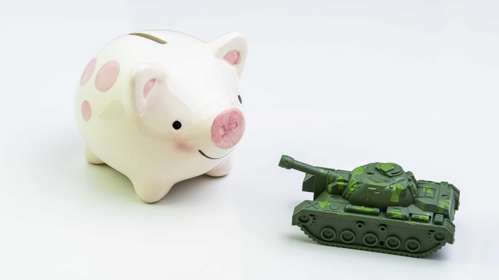 piggy bank next to miniature army tank