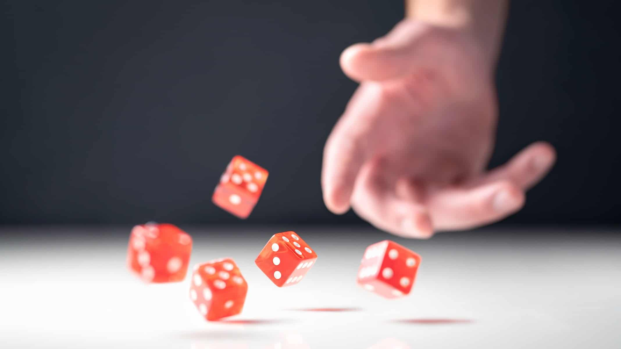 Gaming ASX share price represented by hand throwing four red dice