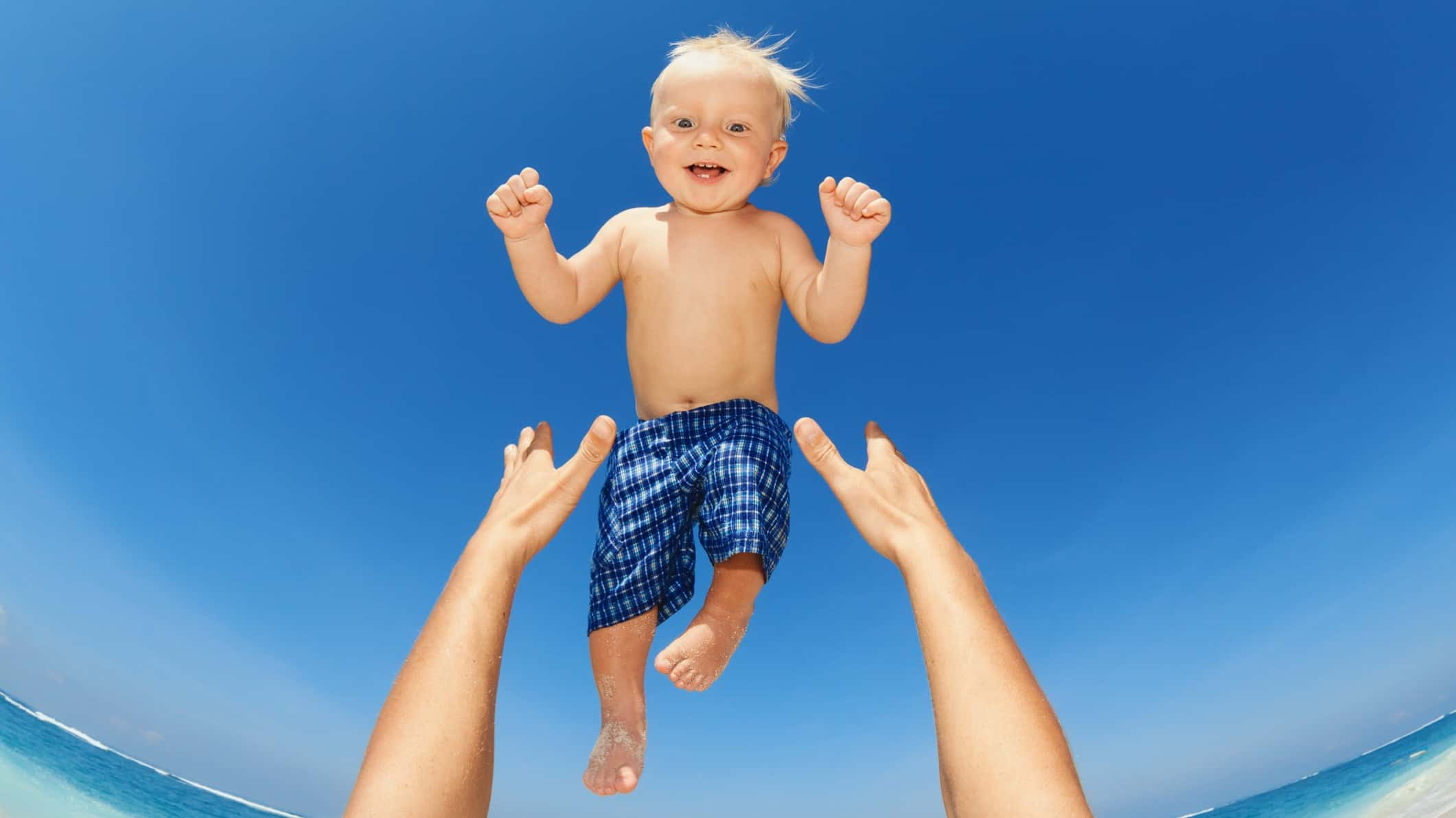 hands throwing smiling baby up in the air representing rising asx share price
