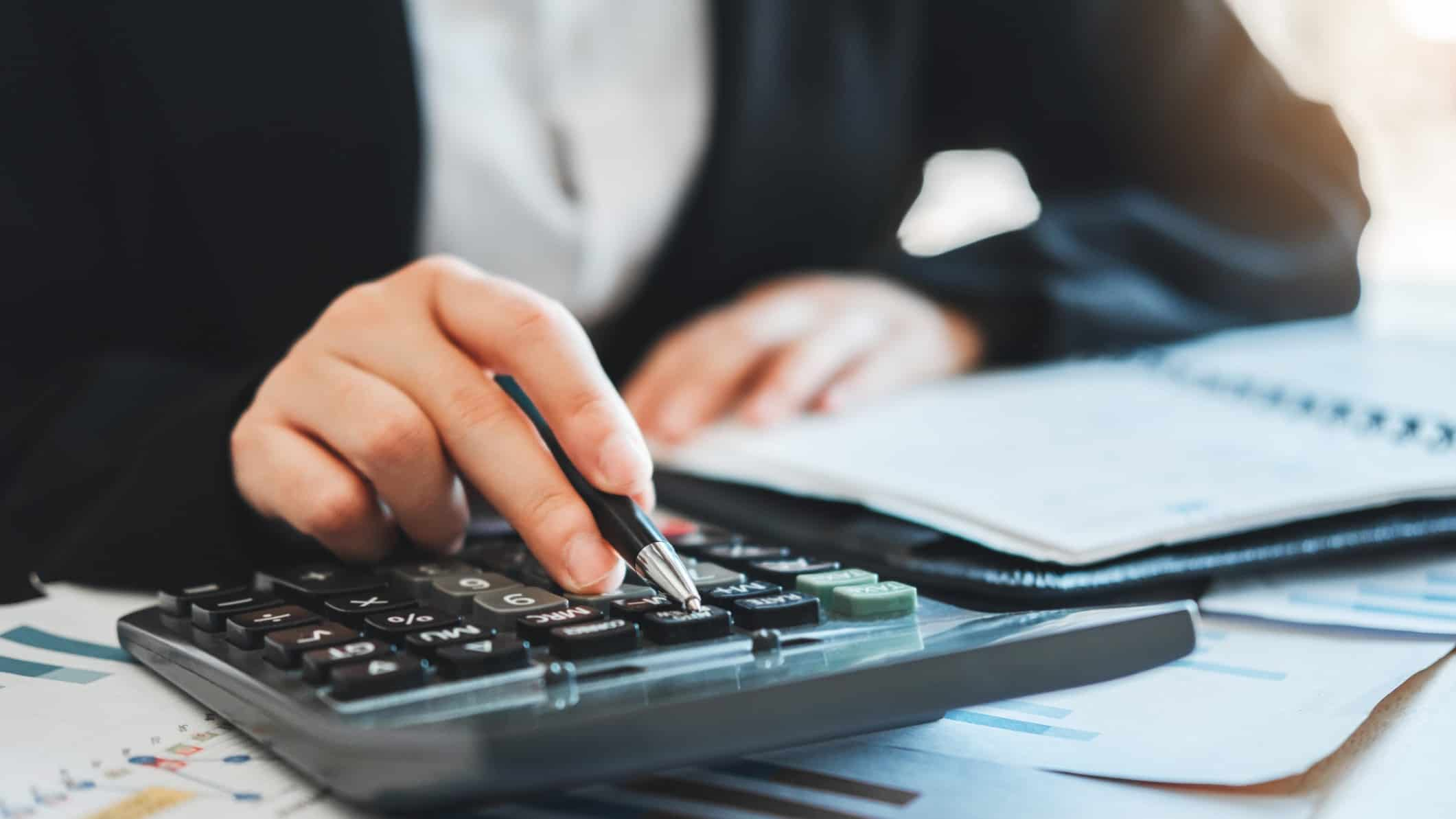 business man reviewing report and using calculator