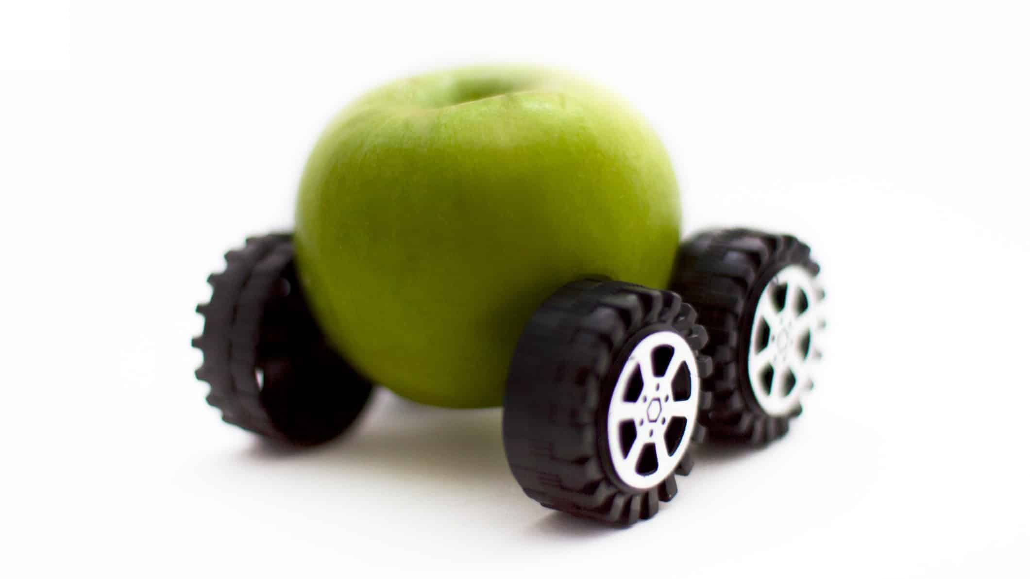 apple and tesla shares represented by image of an apple on wheels