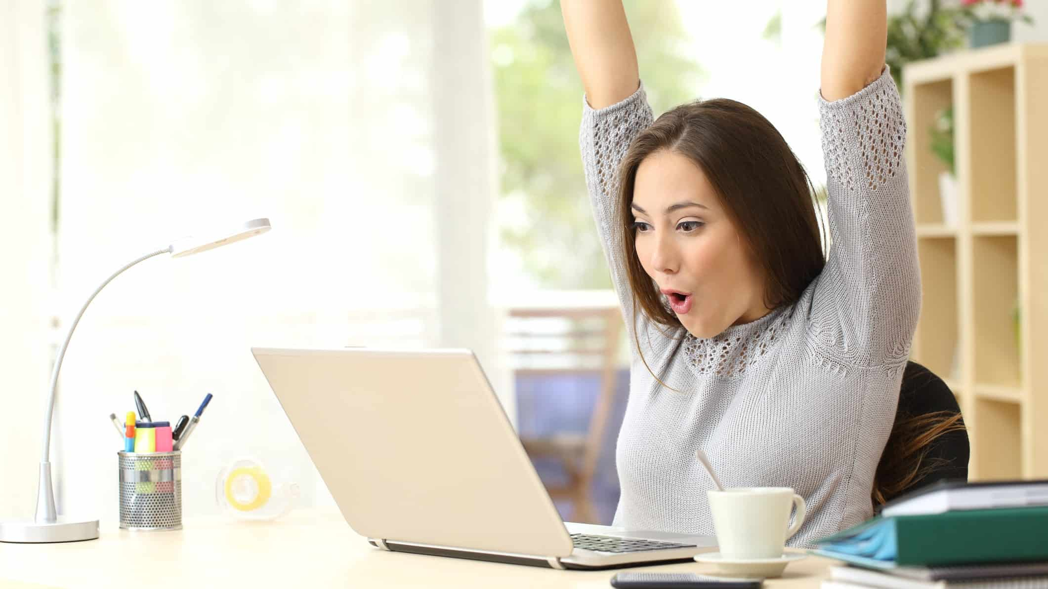 woman throwing arms up in celebration whilst looking at laptop computer