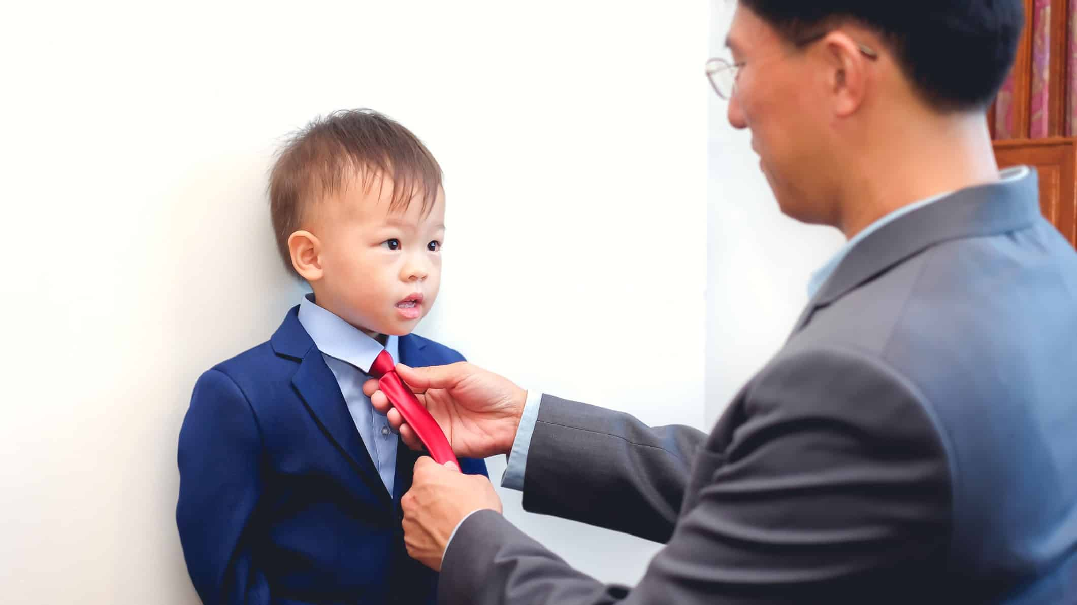 business man adjusting suit and tie on his young son representing a family business