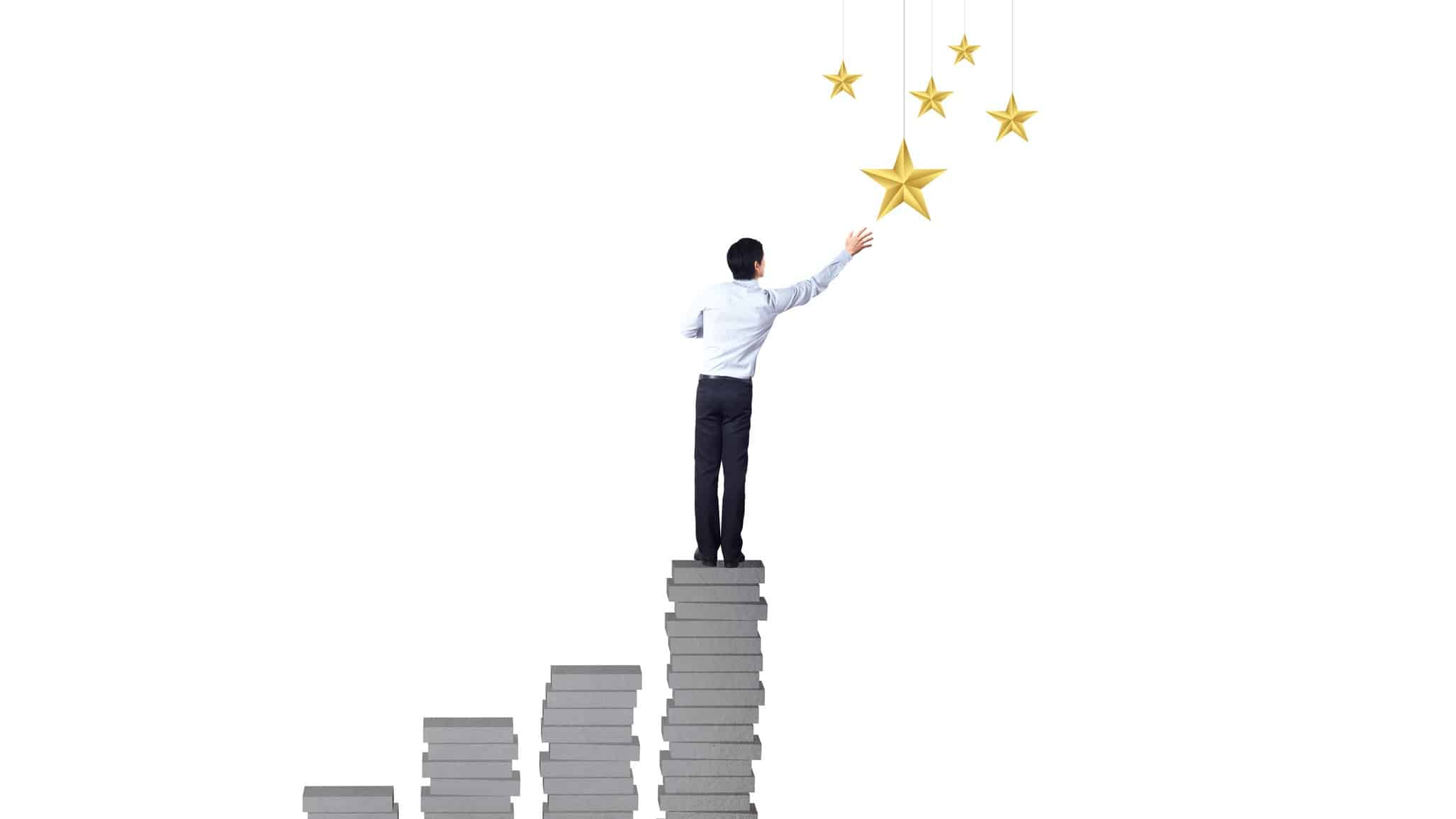 fund manager standing on increasing tiles of bricks reaching for the stars