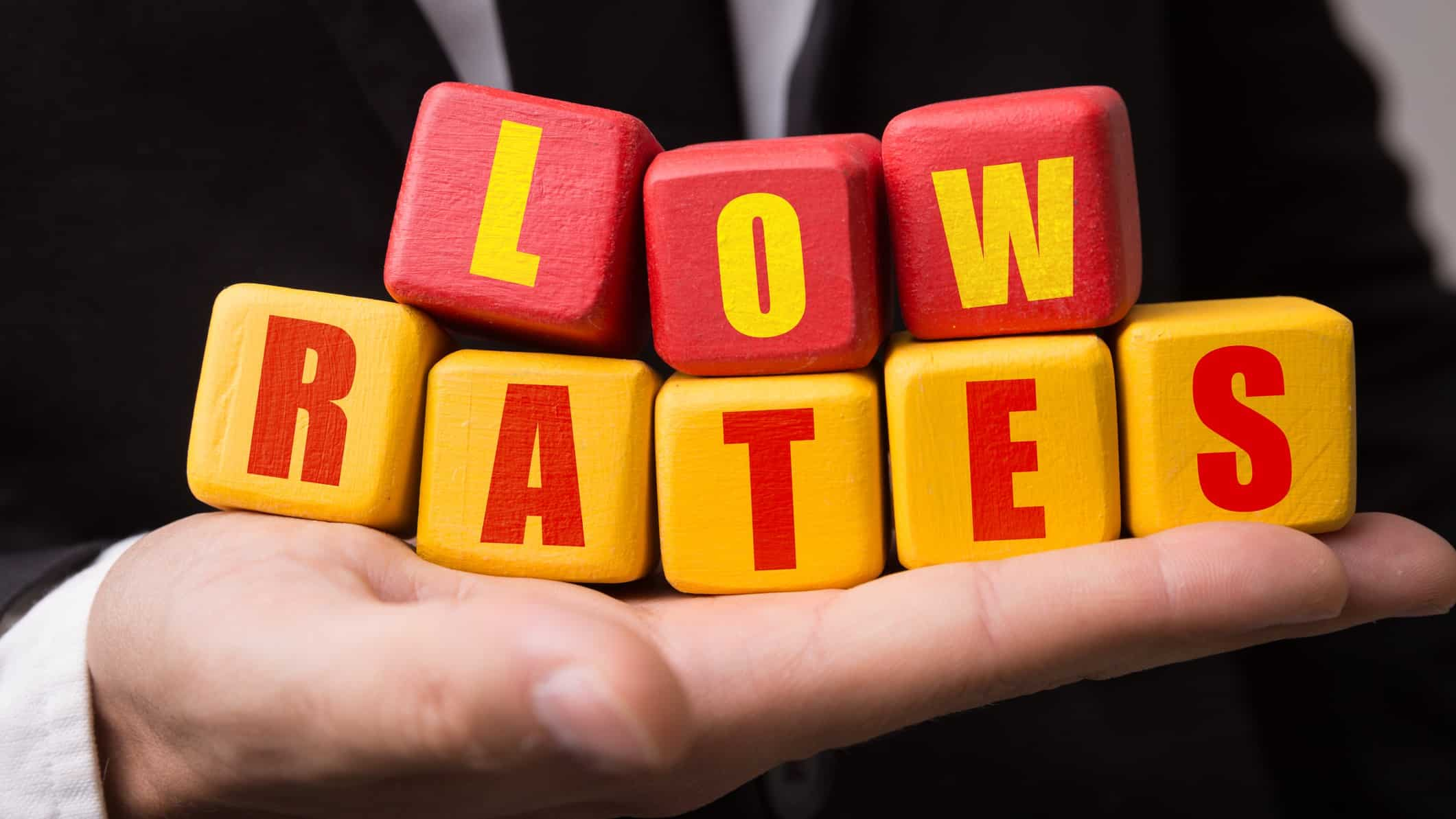 hand holding wooden blocks that spell 'low rates' representing low interest rates