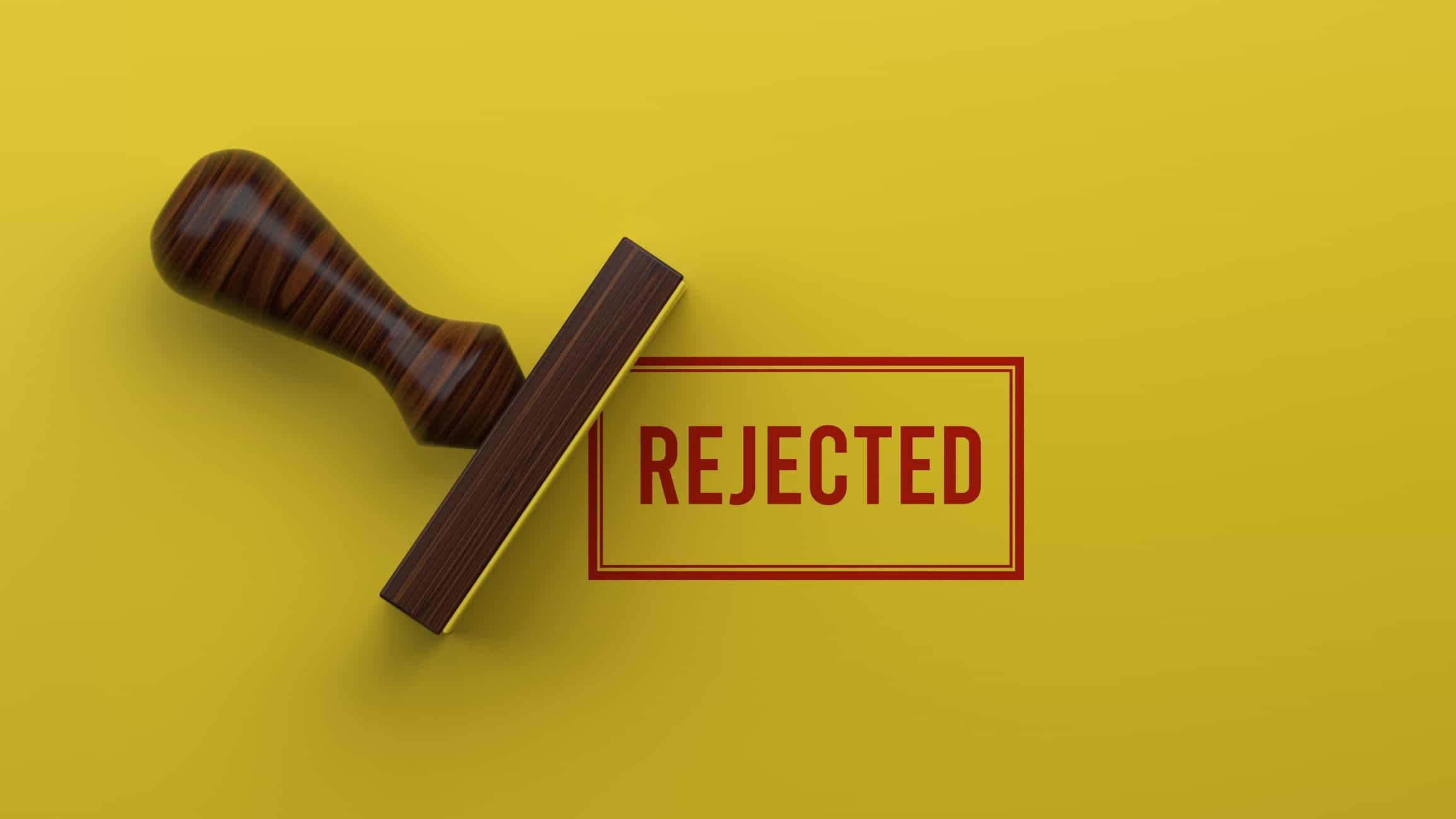 rubber stamp stamping the word 'rejected' on yellow background