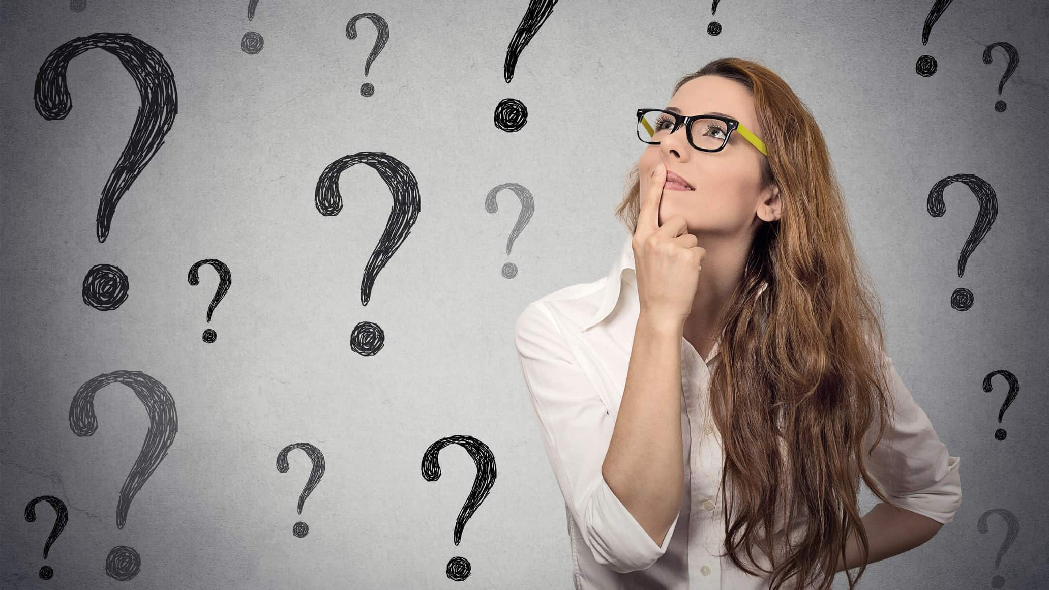 a woman holds her hand to her chin and looks skywards while she is thinking against a backdrop of graphic question marks