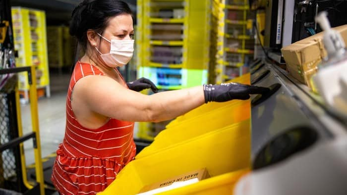 A worker processes Amazon products as the company adds more staff due to growing demand