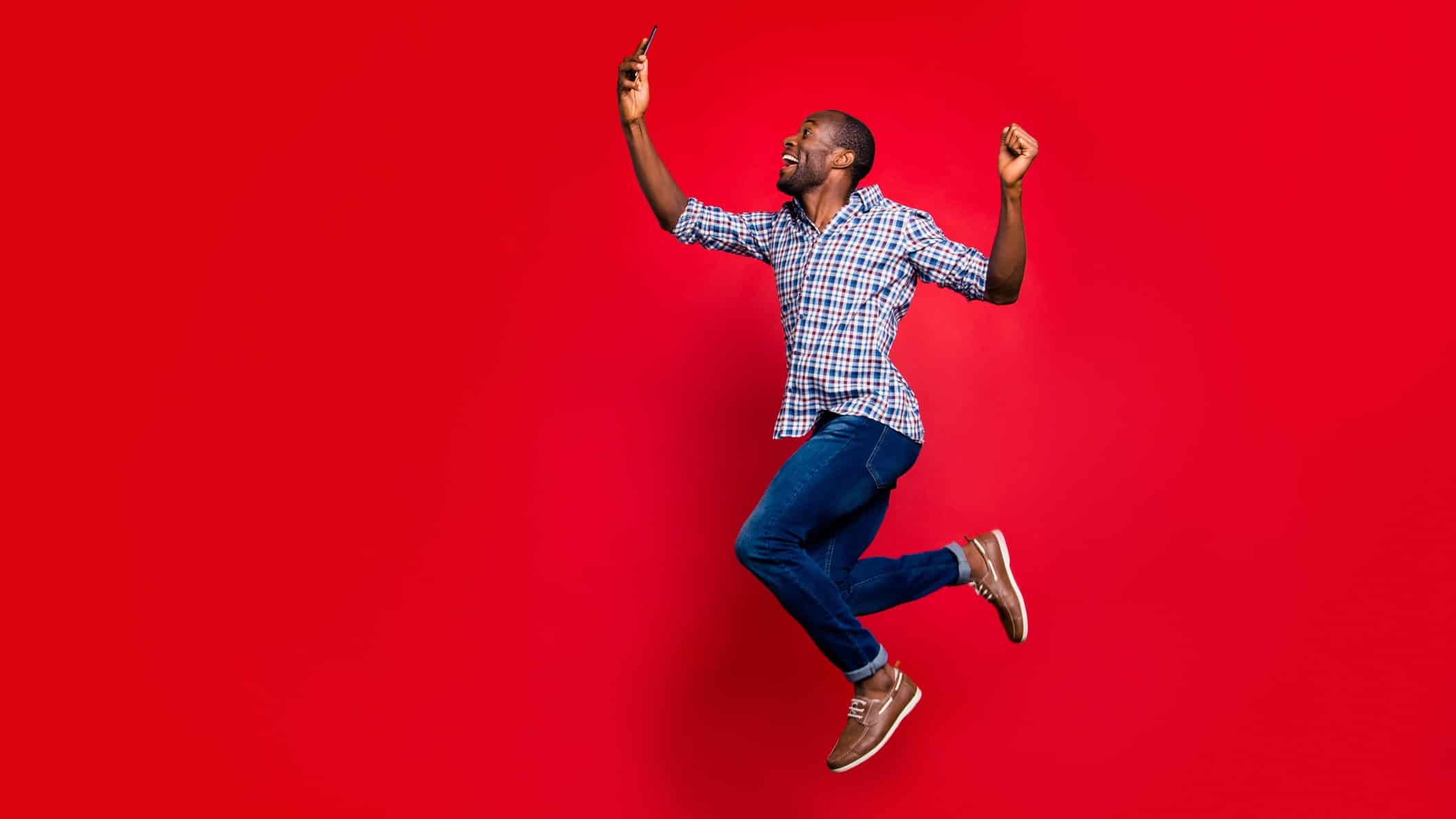 rising ASX share price represented by man jumping in the air for joy looking at mobile phone