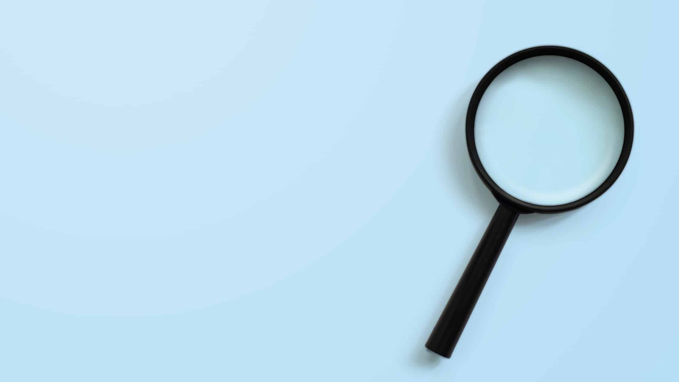 Magnifying glass on blue background symbolising searching for ASX shares