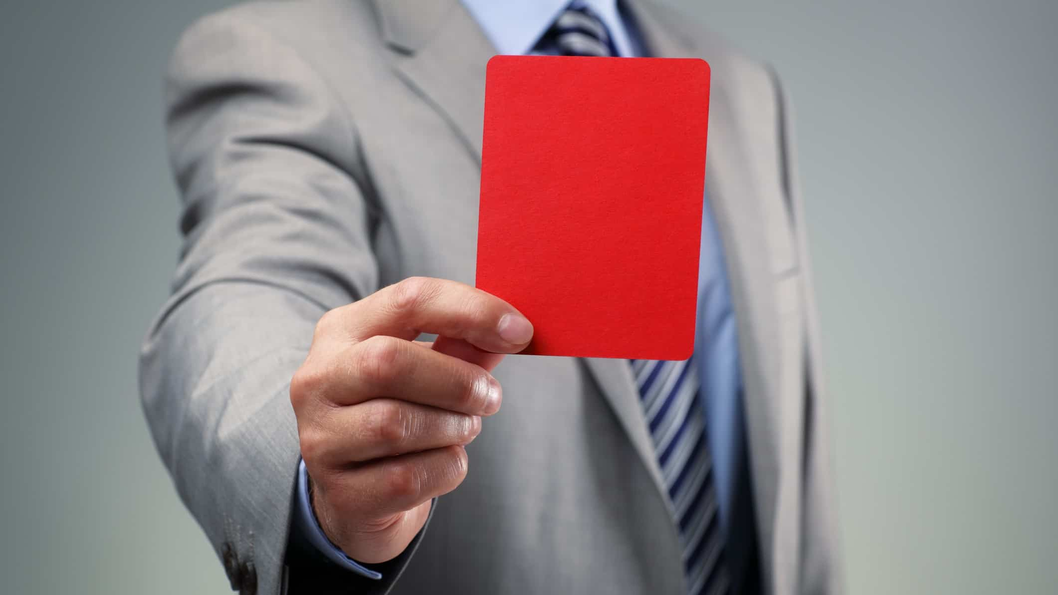 Man in business attire holding up red card to denote a fine