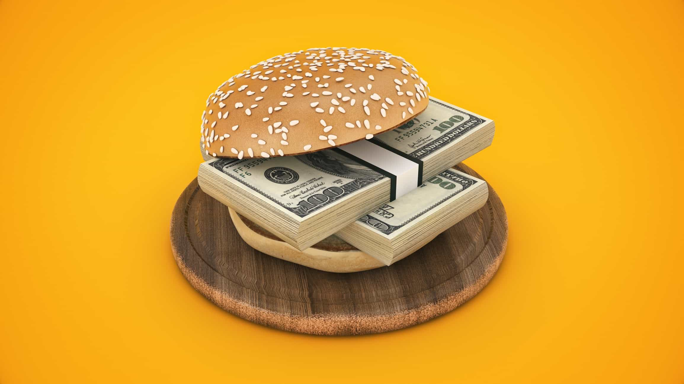 Burger bun around two wads of cash to symbolise food dividend shares
