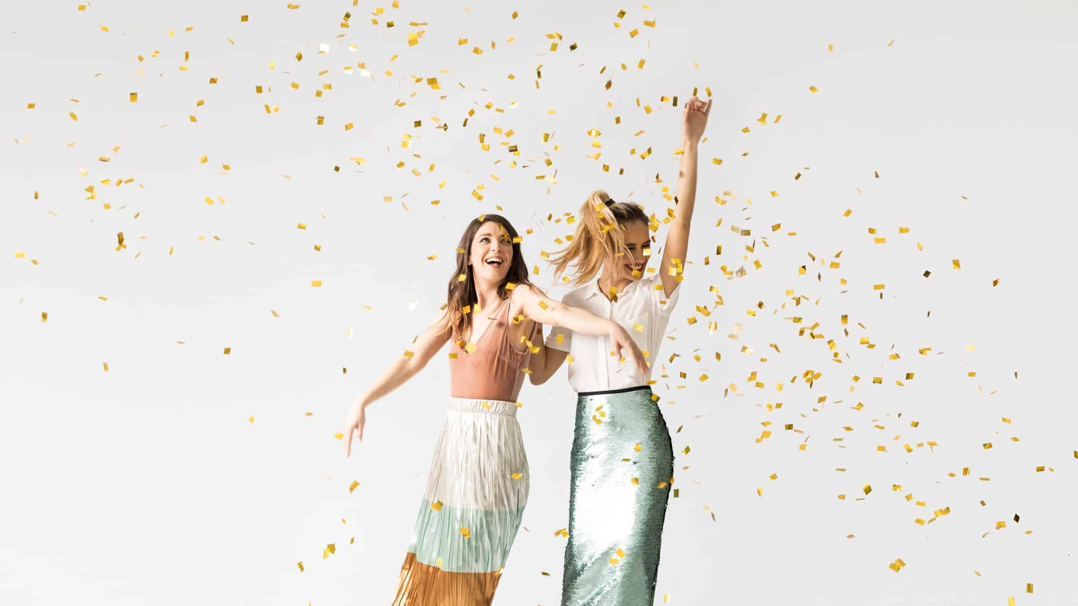 fashion asx share price rise represented by two women dancing among confetti