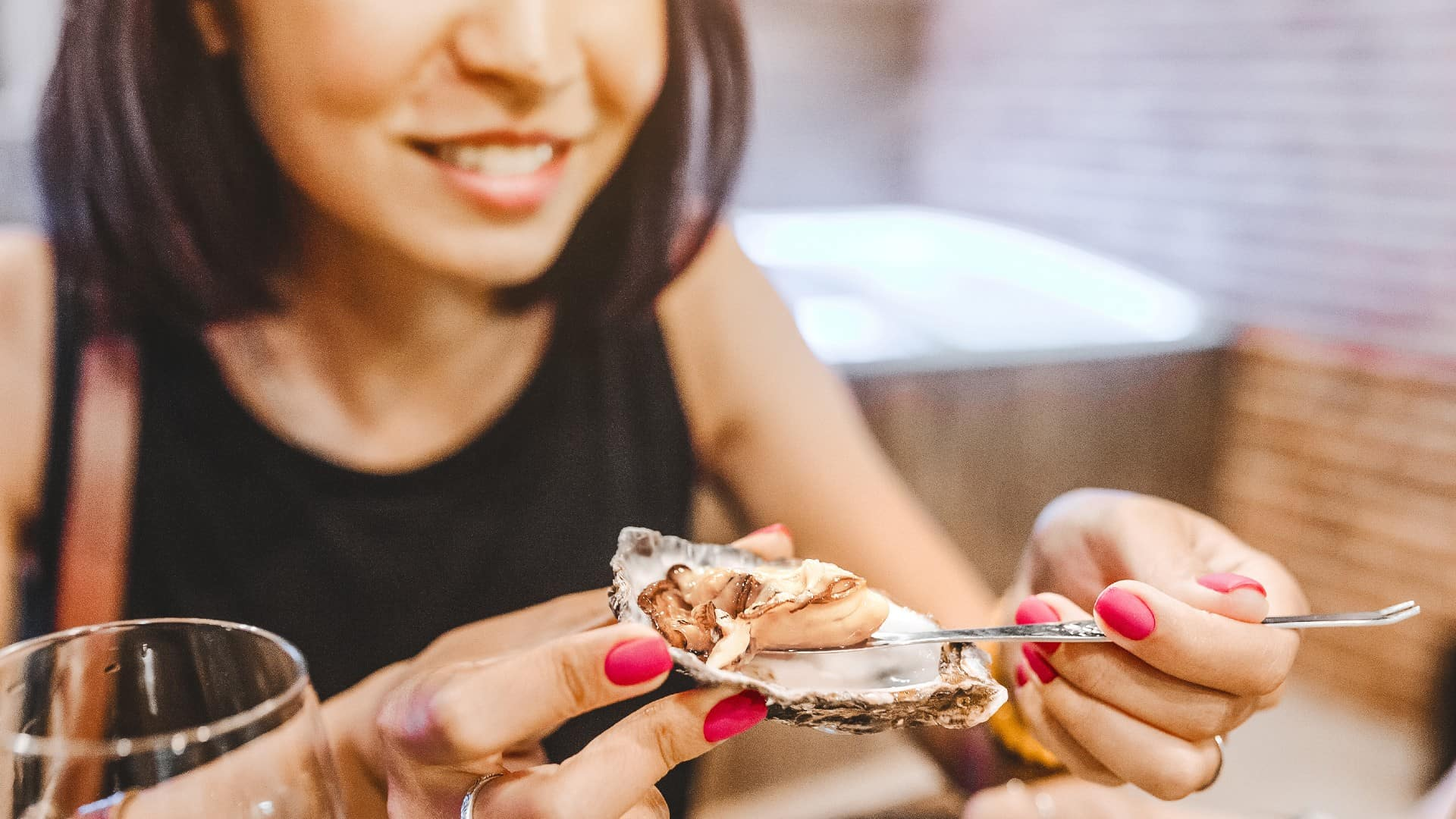 A smiling woman tucks into a fresh rock oyster, indicating a positive share price