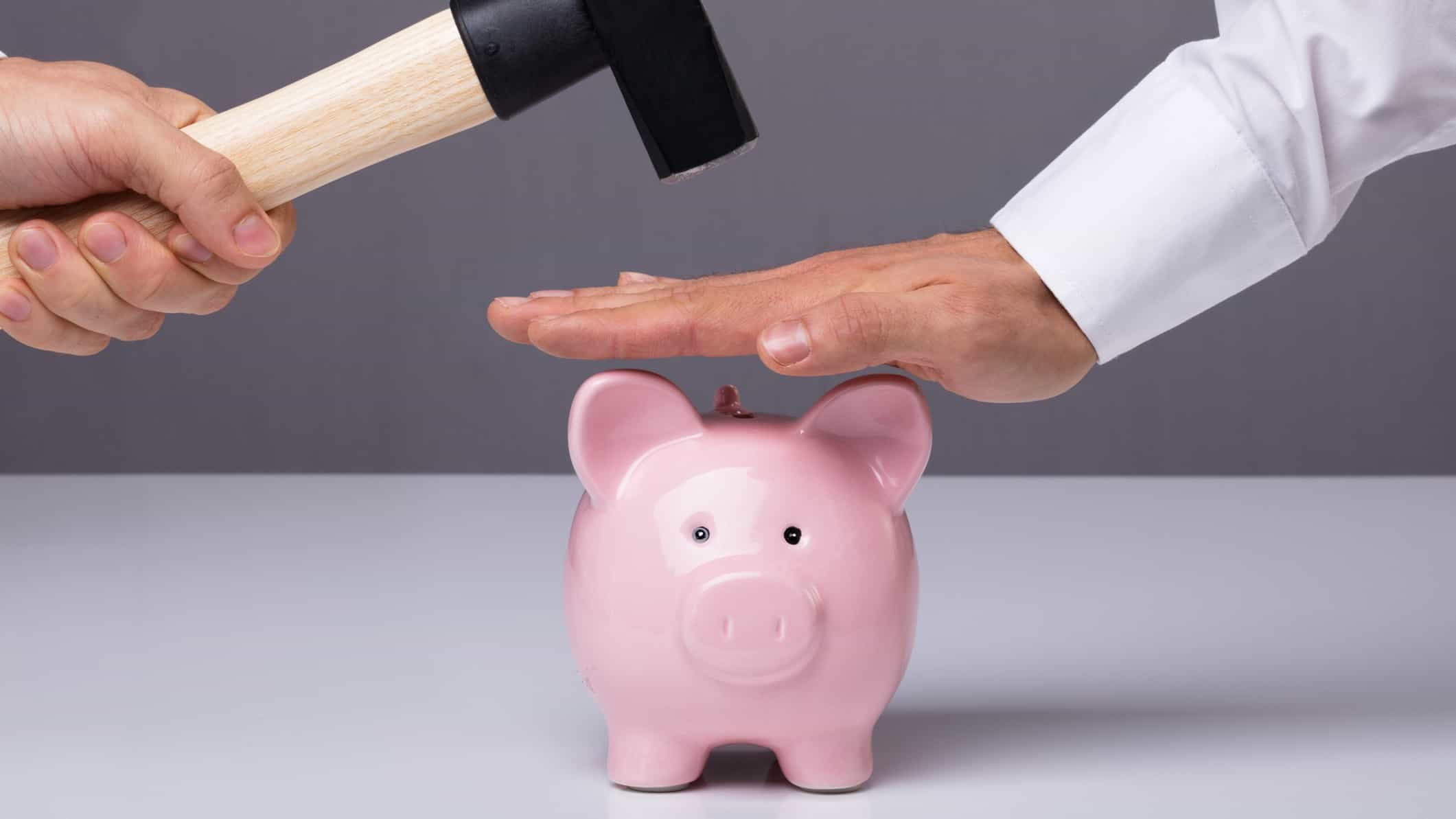 A hand protecting a pink piggy bank from being smashed by a hammer, representing the prevention of bank or government raids on super