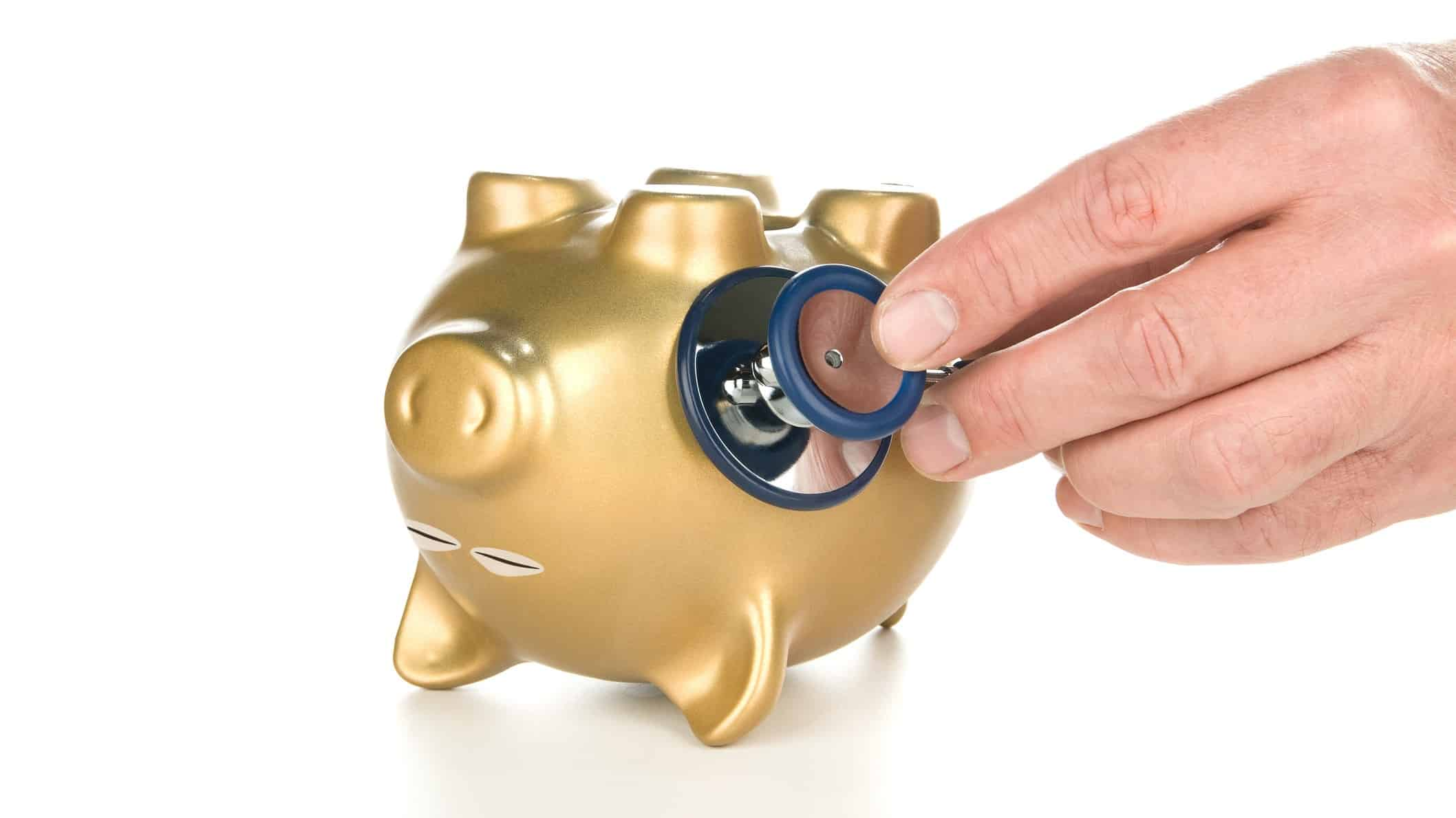 whether recessions cause deaths represented by docotor checking heart rate of upturned piggy bank
