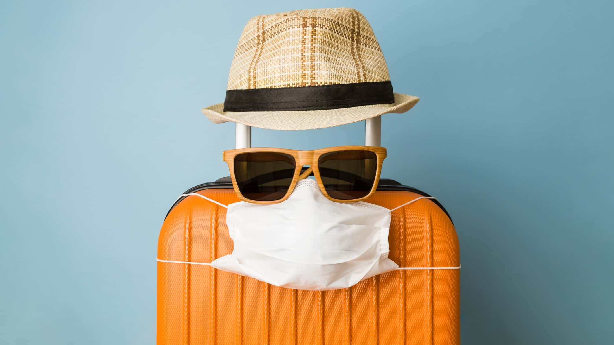 travel asx share price represented by suitcase wearing covid mask
