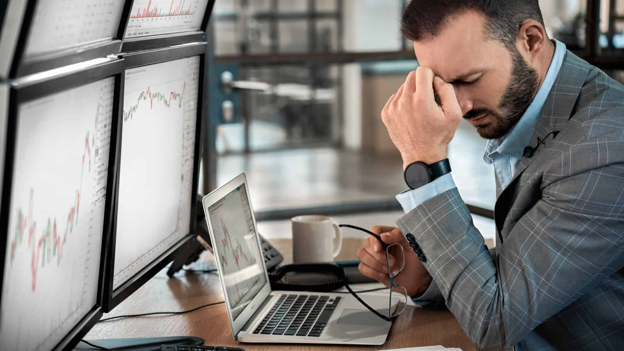 A businessman in front of a computer with his head on his hand in disbelief, indicating poor IPO or share price performance