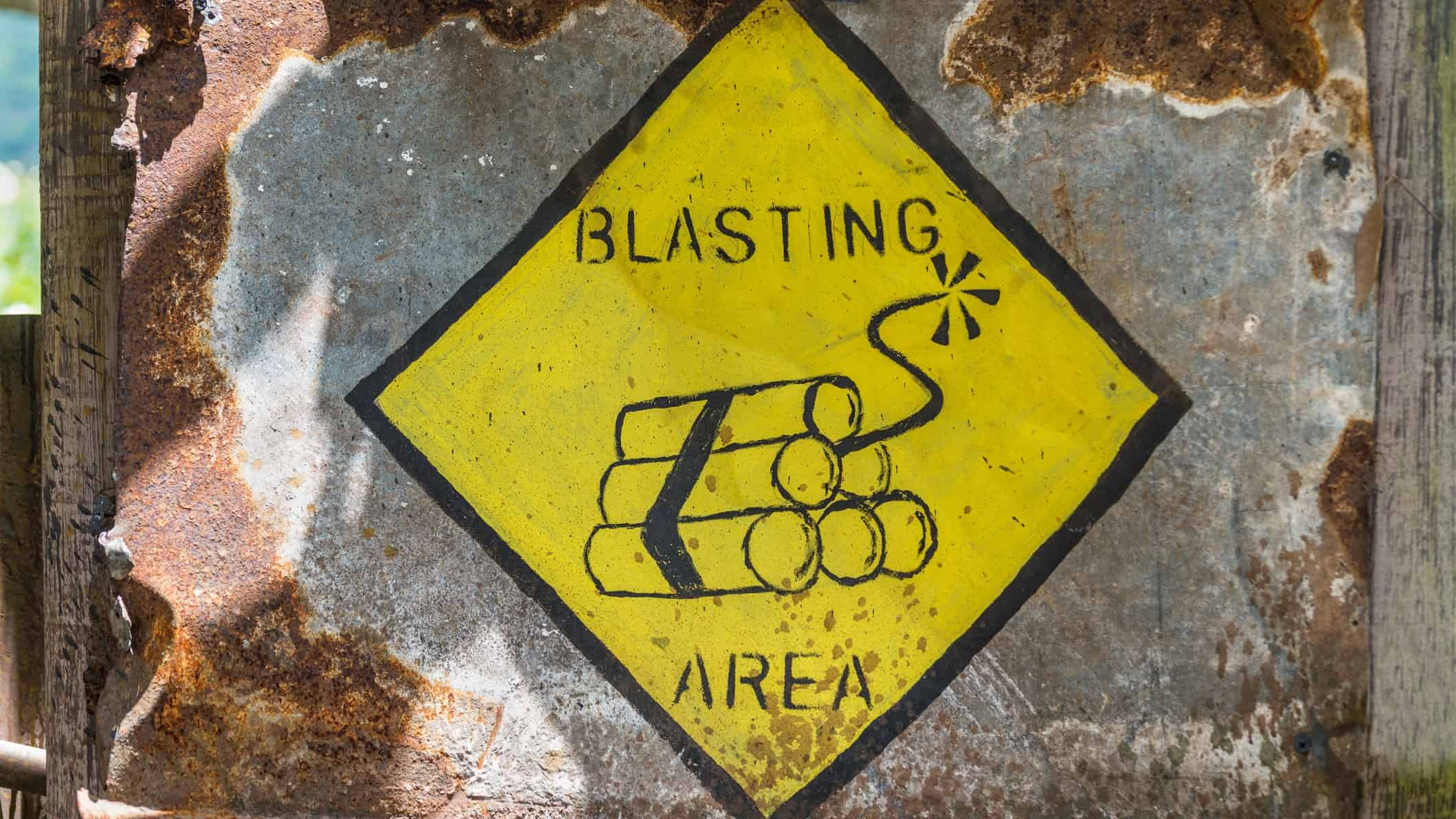 mining asx share price represented by yellow sign stating blasting area downgrade