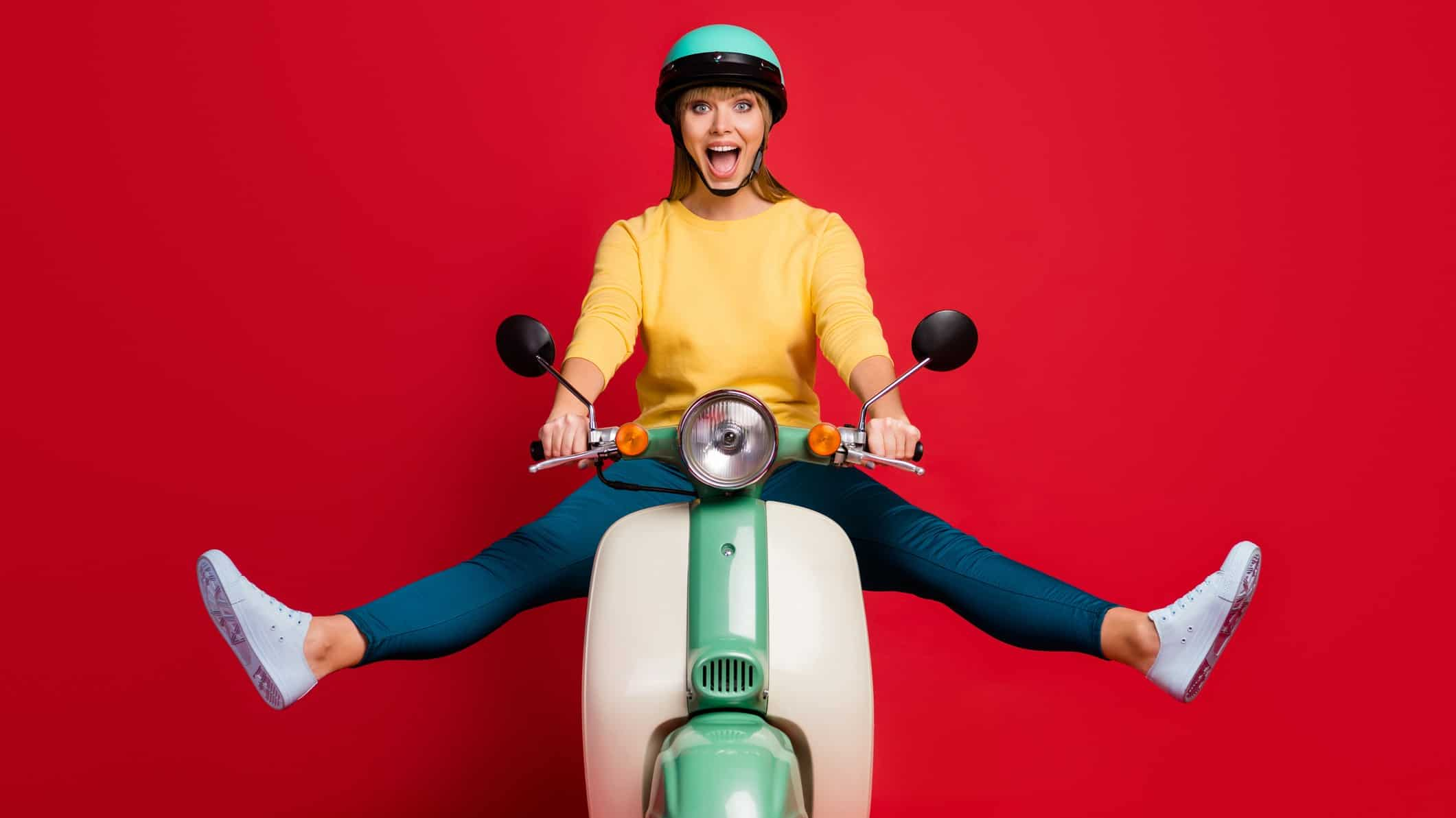 Excited woman on scooter wearing helmet in front of red background