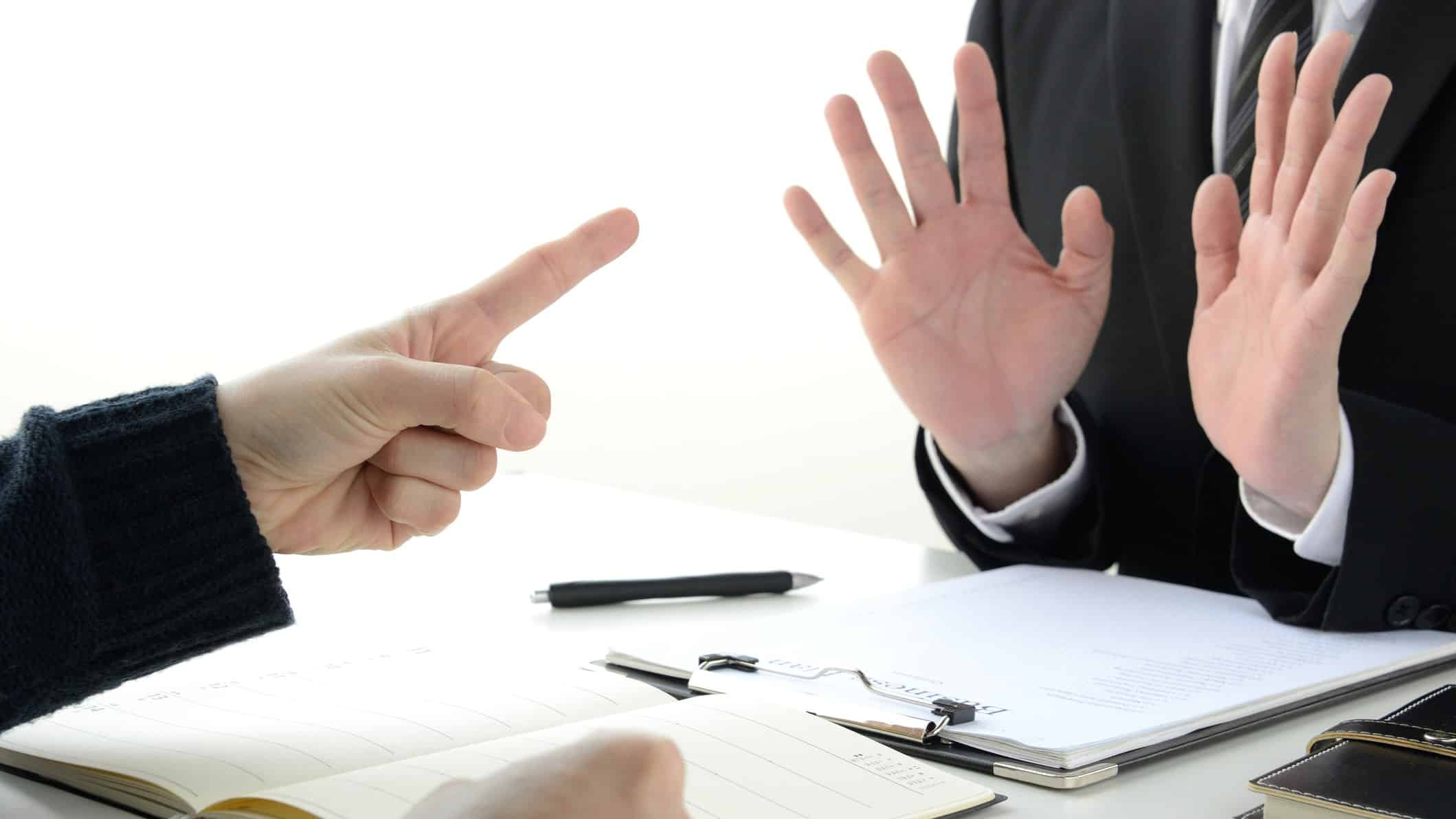 Two buisnessmen: one poining a finger, the other holding his hands up in denial