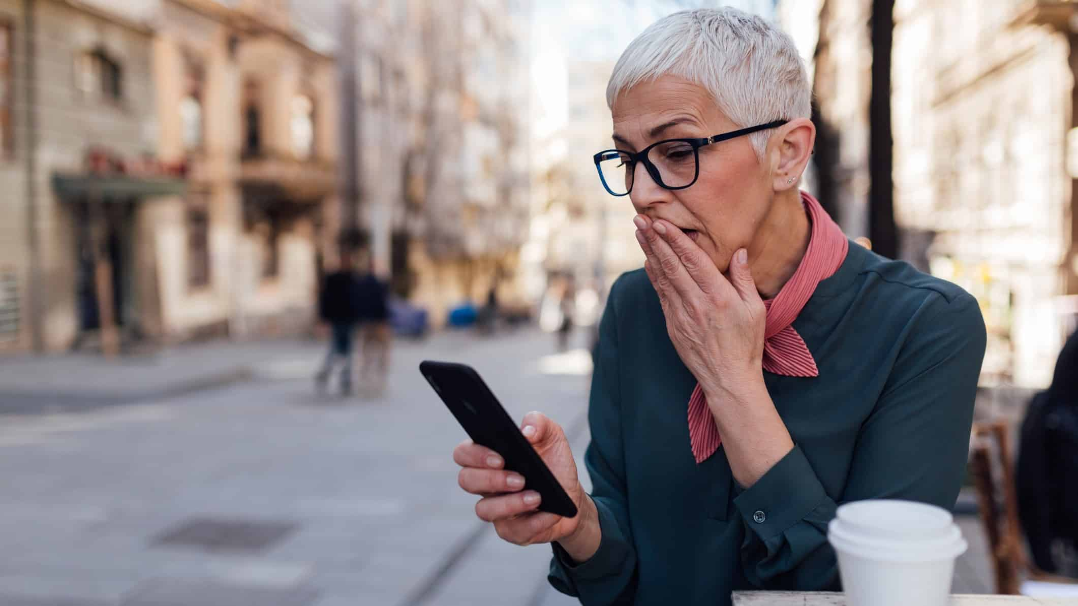 Falling ASX share price represented by woman looking shocked at mobile phone