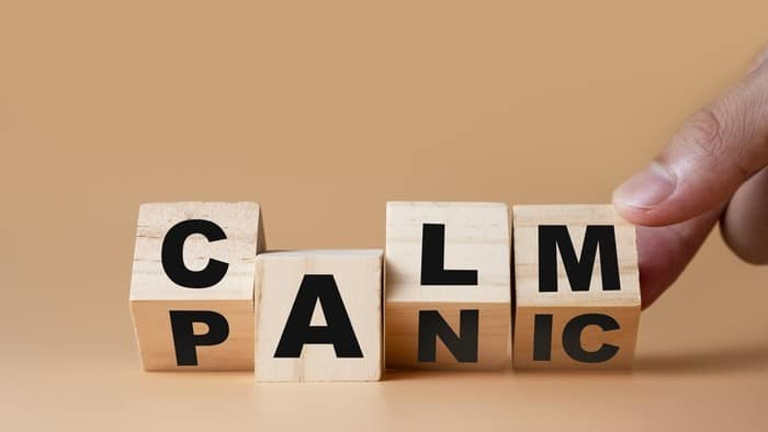 falling nasdaq and asx share price represented by wooden blocks spelling calm and panic