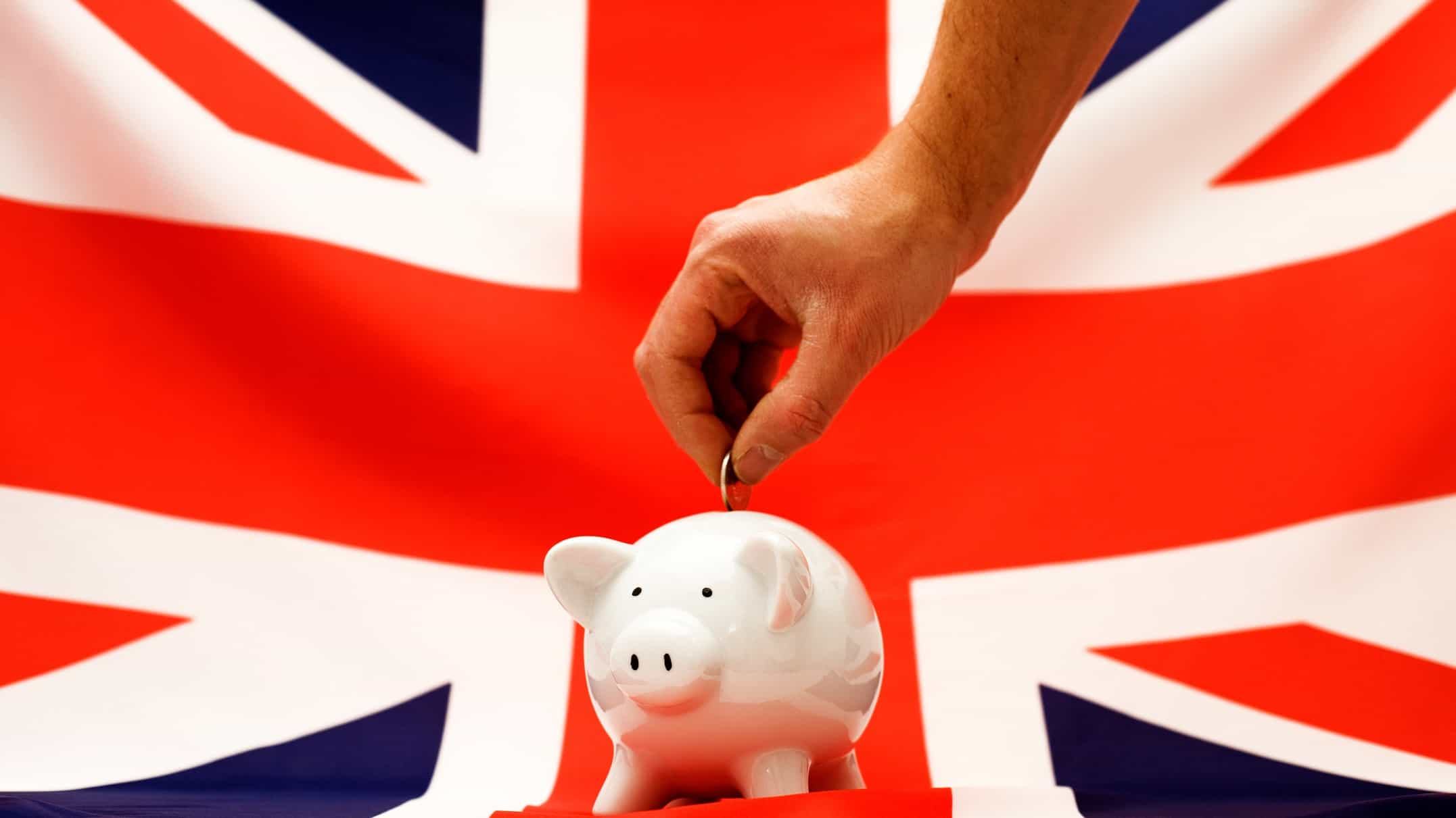 Investing in ftse 100 represented by investor placing money in piggy bank in front of English flag