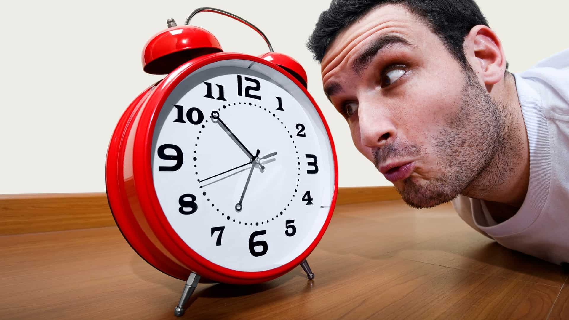 A man closesly watch a clock, indicating a delay or timing issue on an ASX share price movement