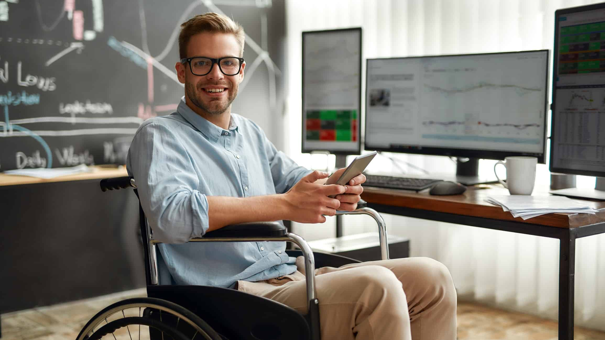 Smiling man with phone in wheelchair watching stocks and trends on computer