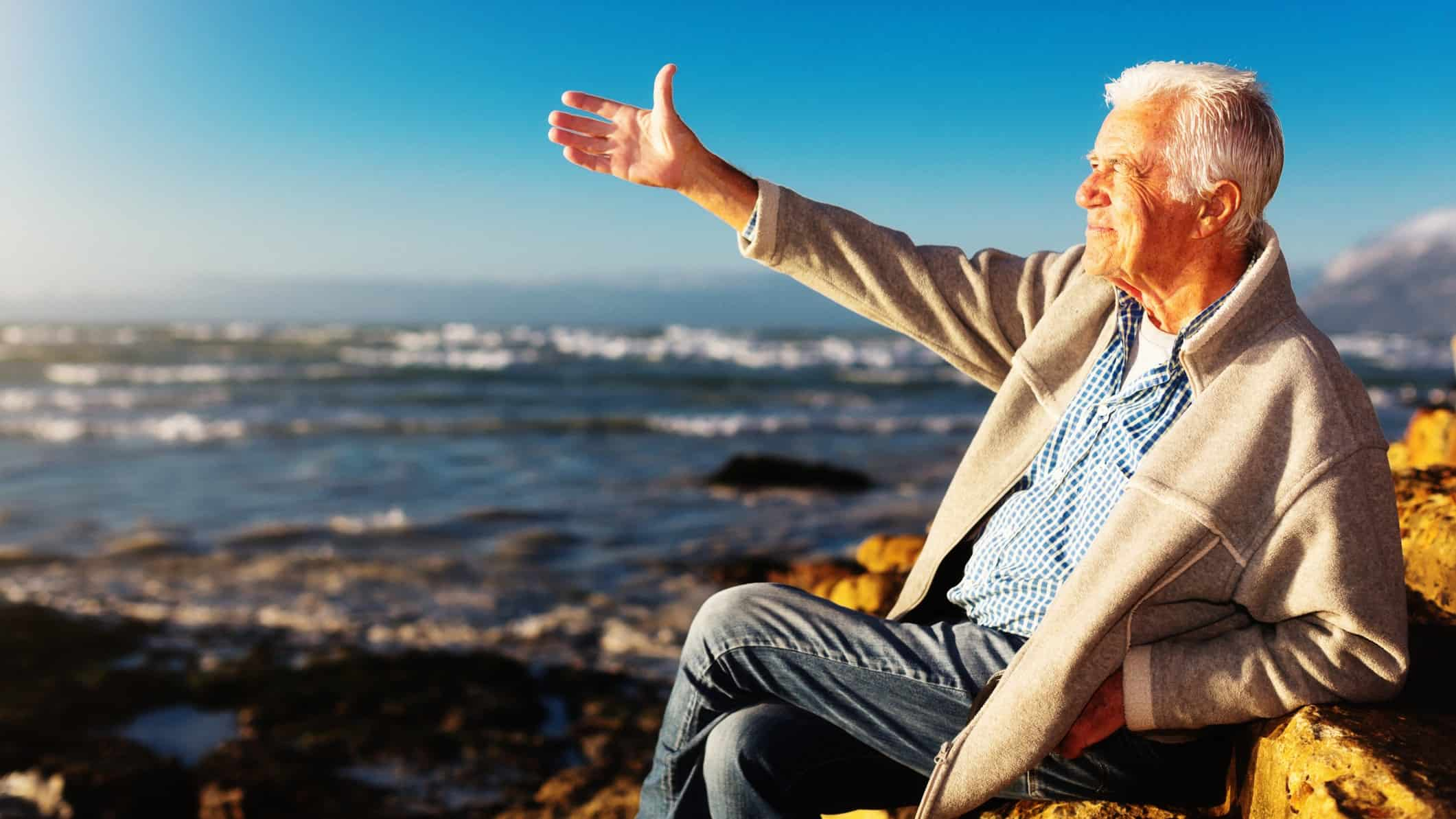 A mature aged man sits on a rock at the beach, indicating ways to build wealth after 50