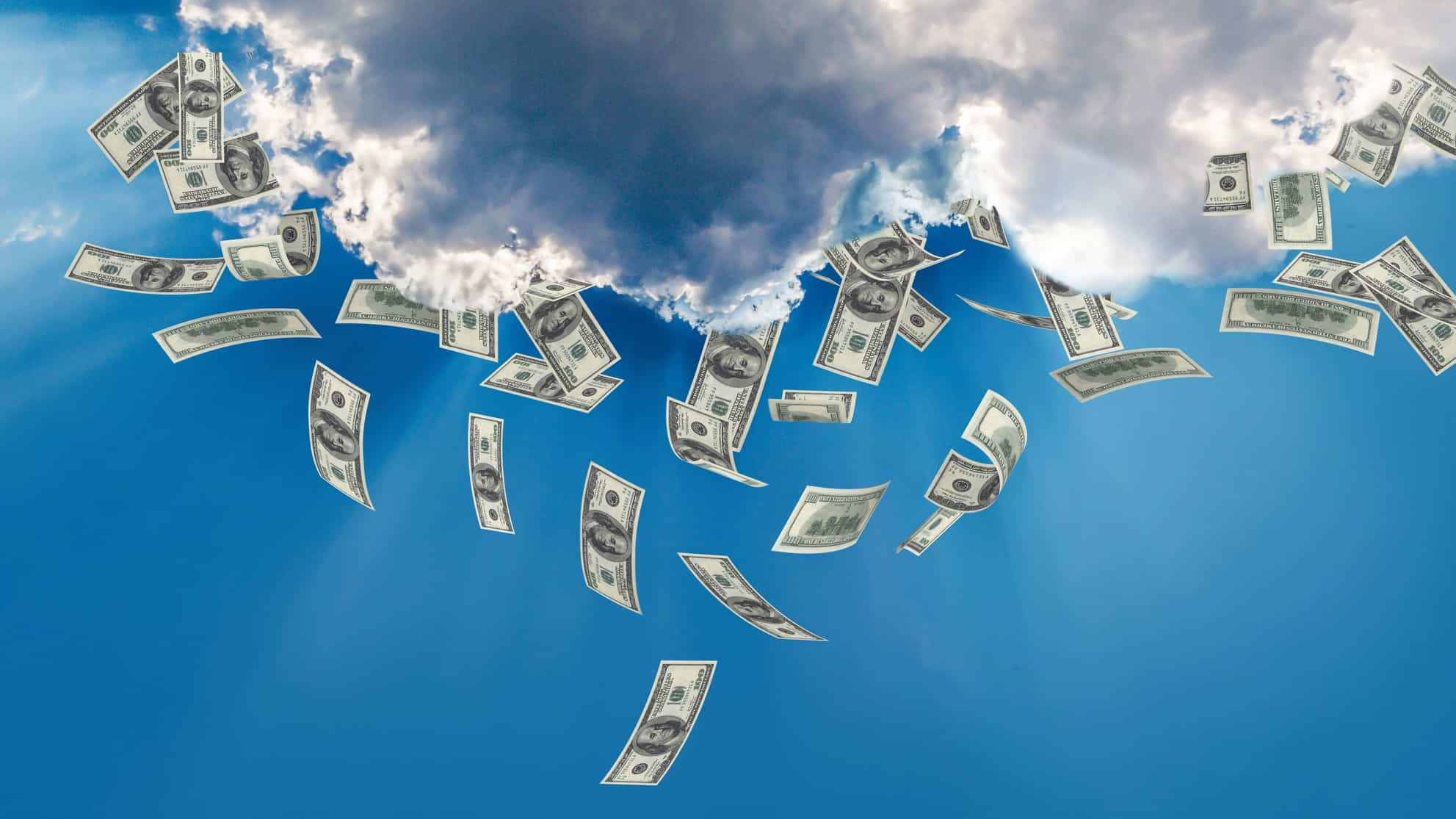 Cloud against blue sky with cash falling from it