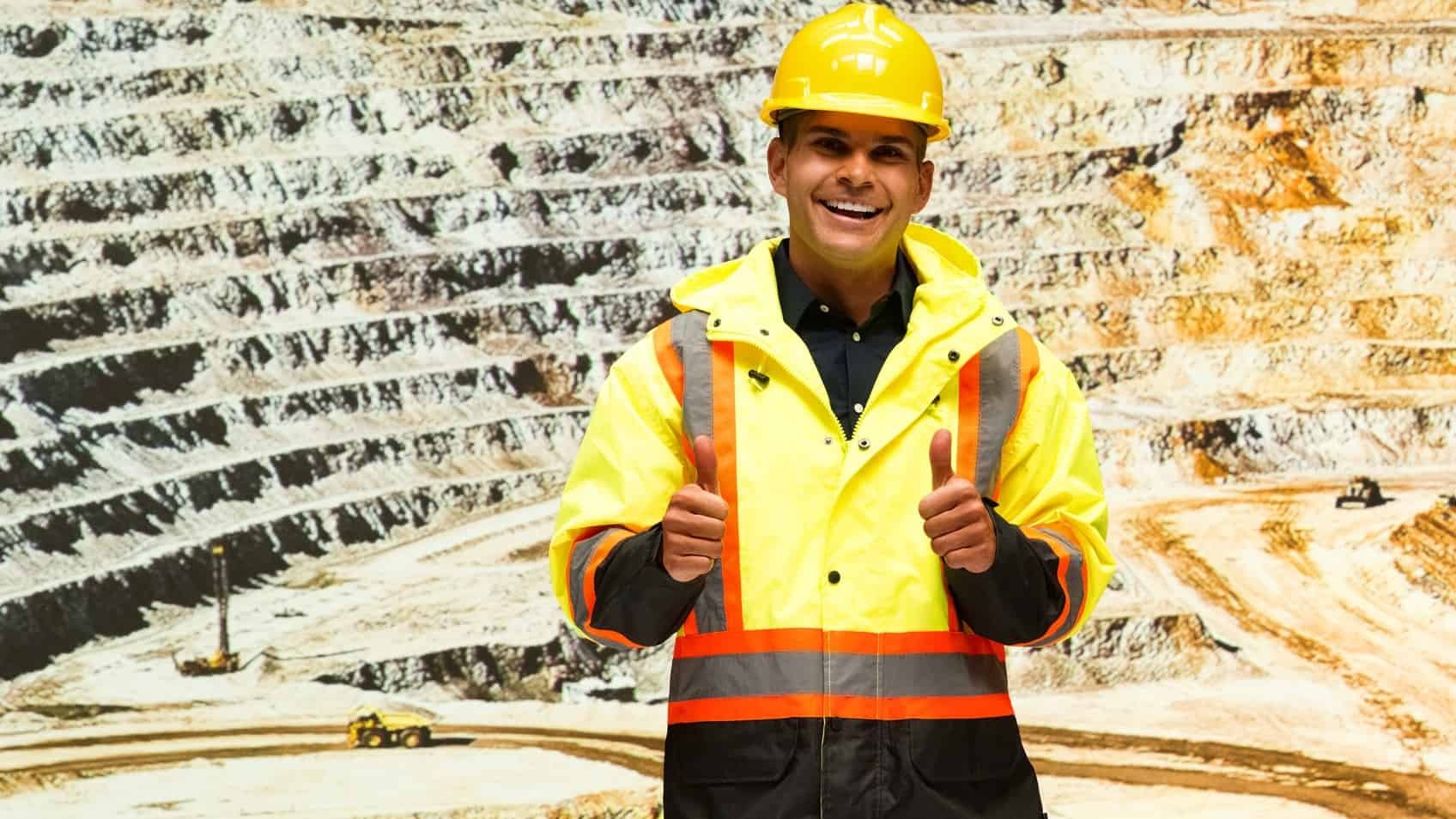 A happy minner does the thumbs up in front of an open pit copper mine, indicating a surging share price in ASX mining shares