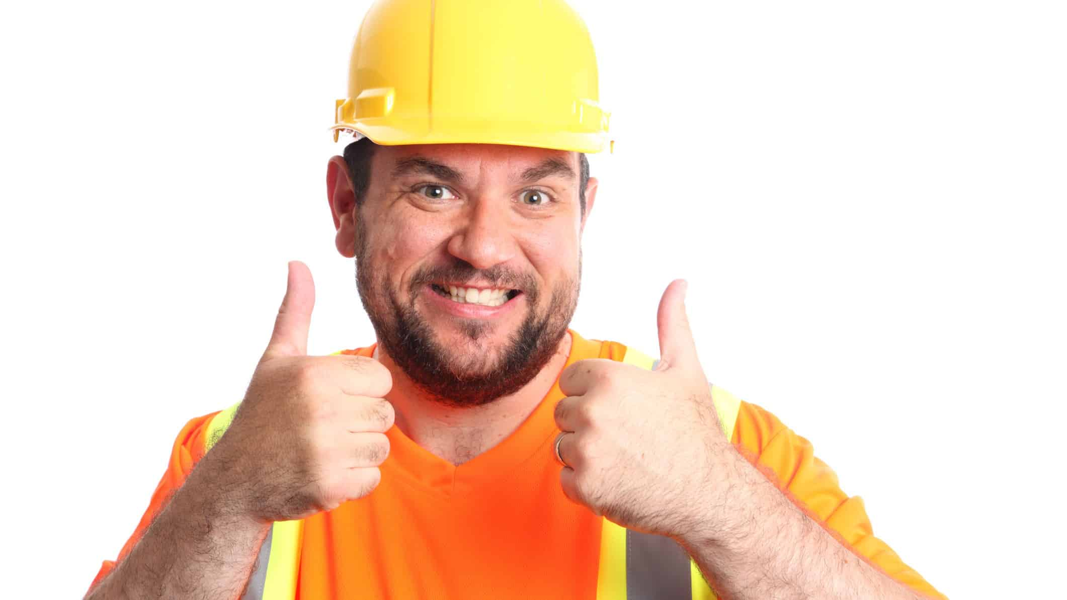 Mining worker wearing hard hat and high vis vest holds thumbs up and smiles
