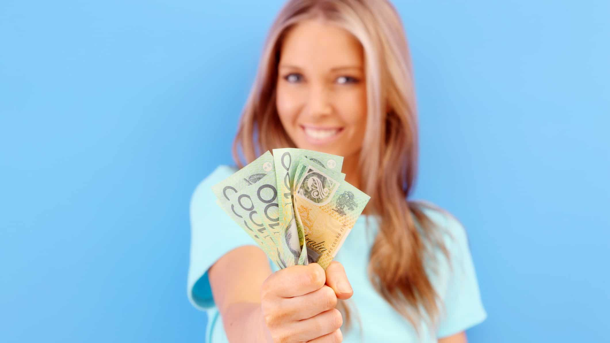 A smiling woman with a handful of $100 notes, inidcating strong share price gains