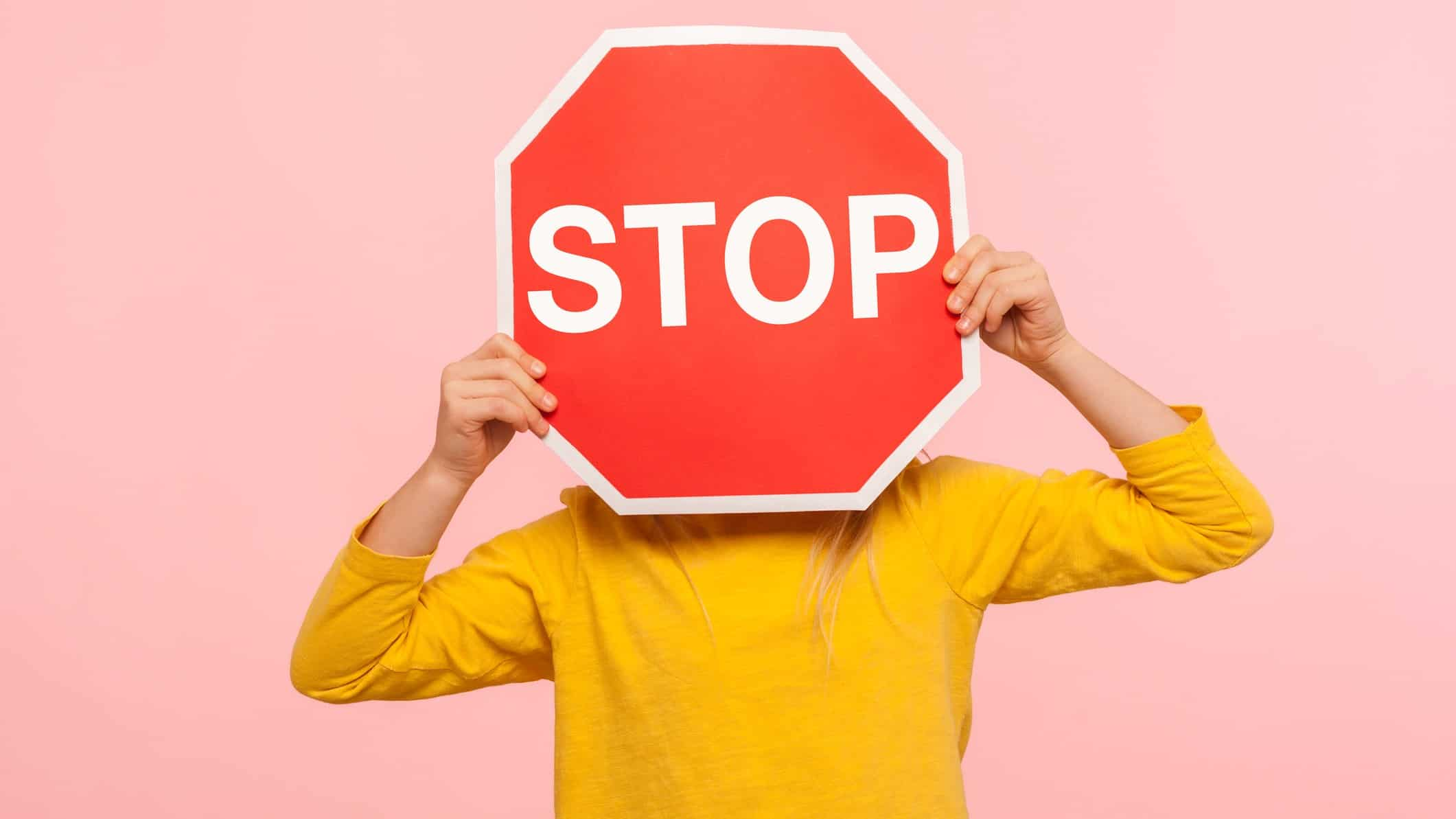 A person holds a stop sign in front of their head