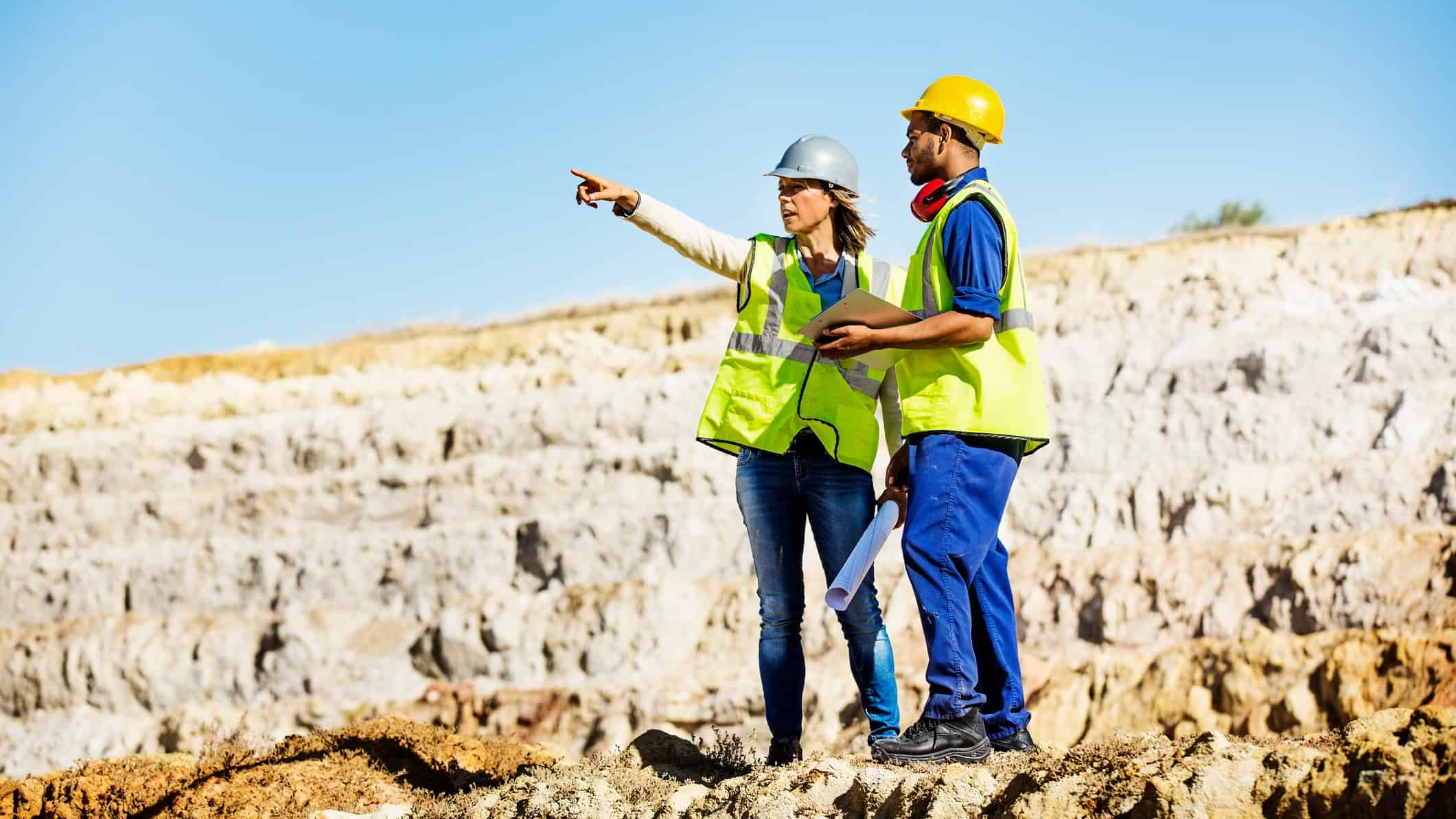 Commodities premium ASX shares Female miner and male miner stand in open mine pit surveying the area