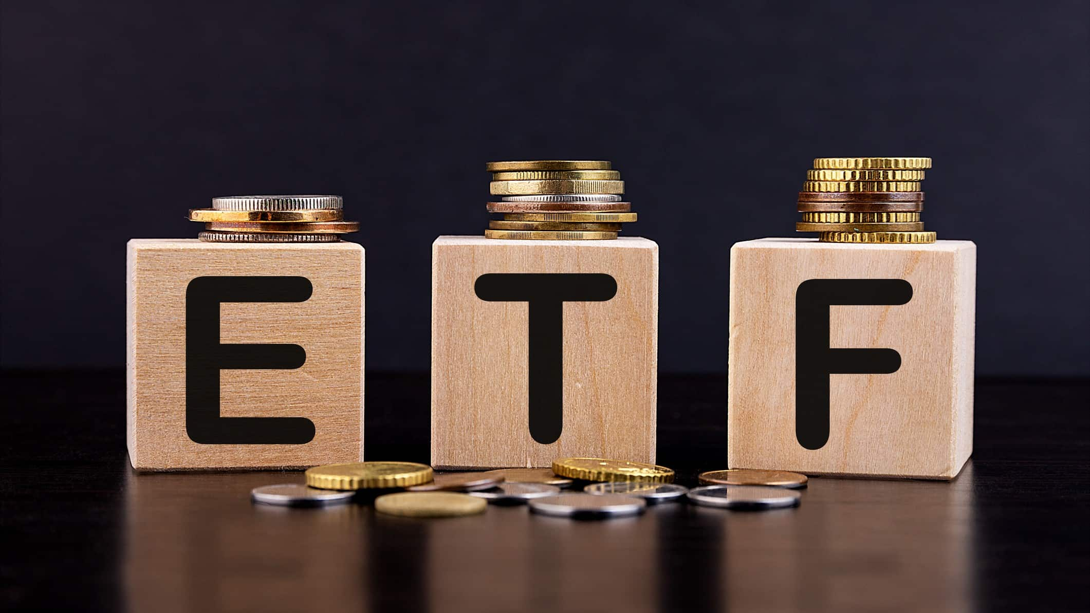 The letters ETF on wooden cubes with golden coins on top of the cubes and on the ground