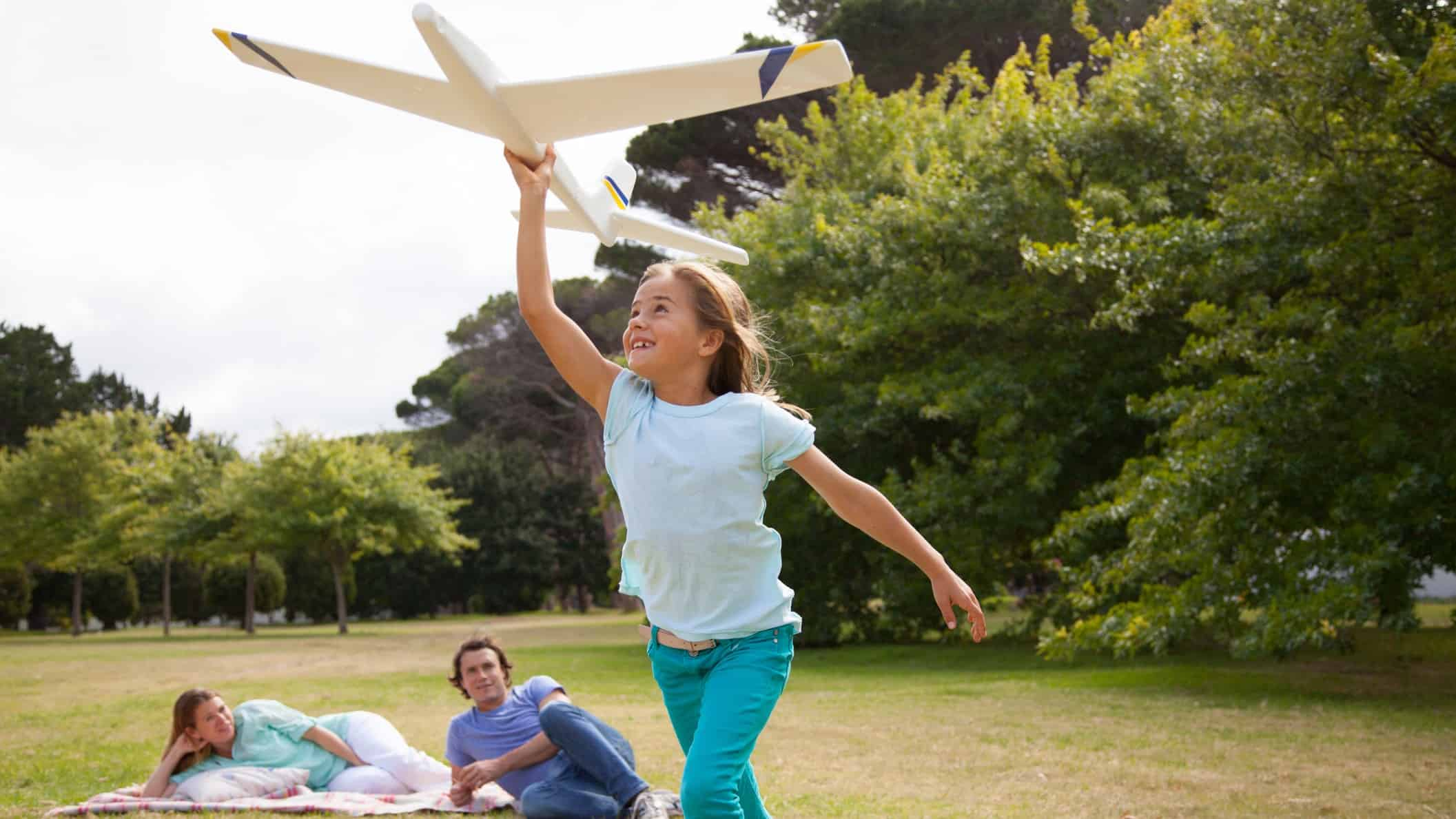 A girl runs with model plane in a park with her parents in the background lying on the grass watching her.