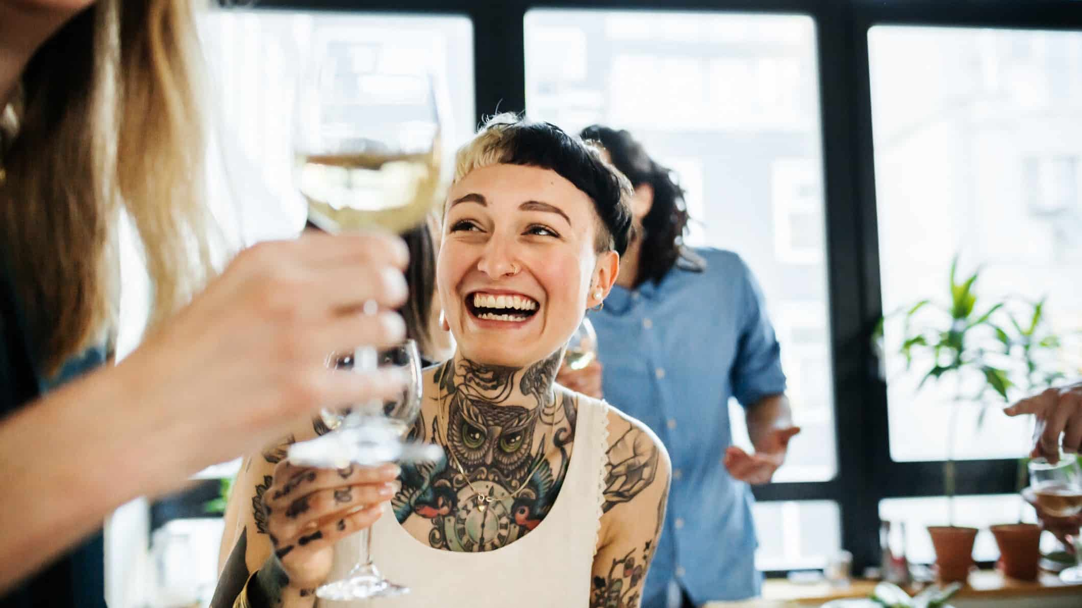Smiling person with tattoos enjoying a glass of wine with a group of others.
